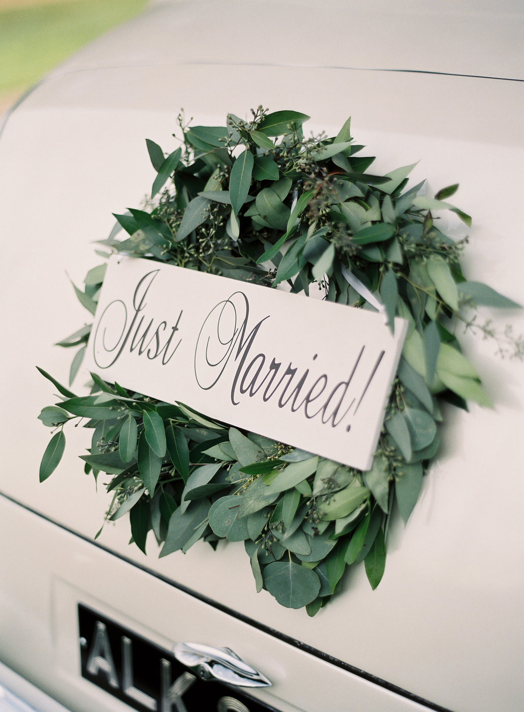wedding wreath attached to getaway car with just married sign
