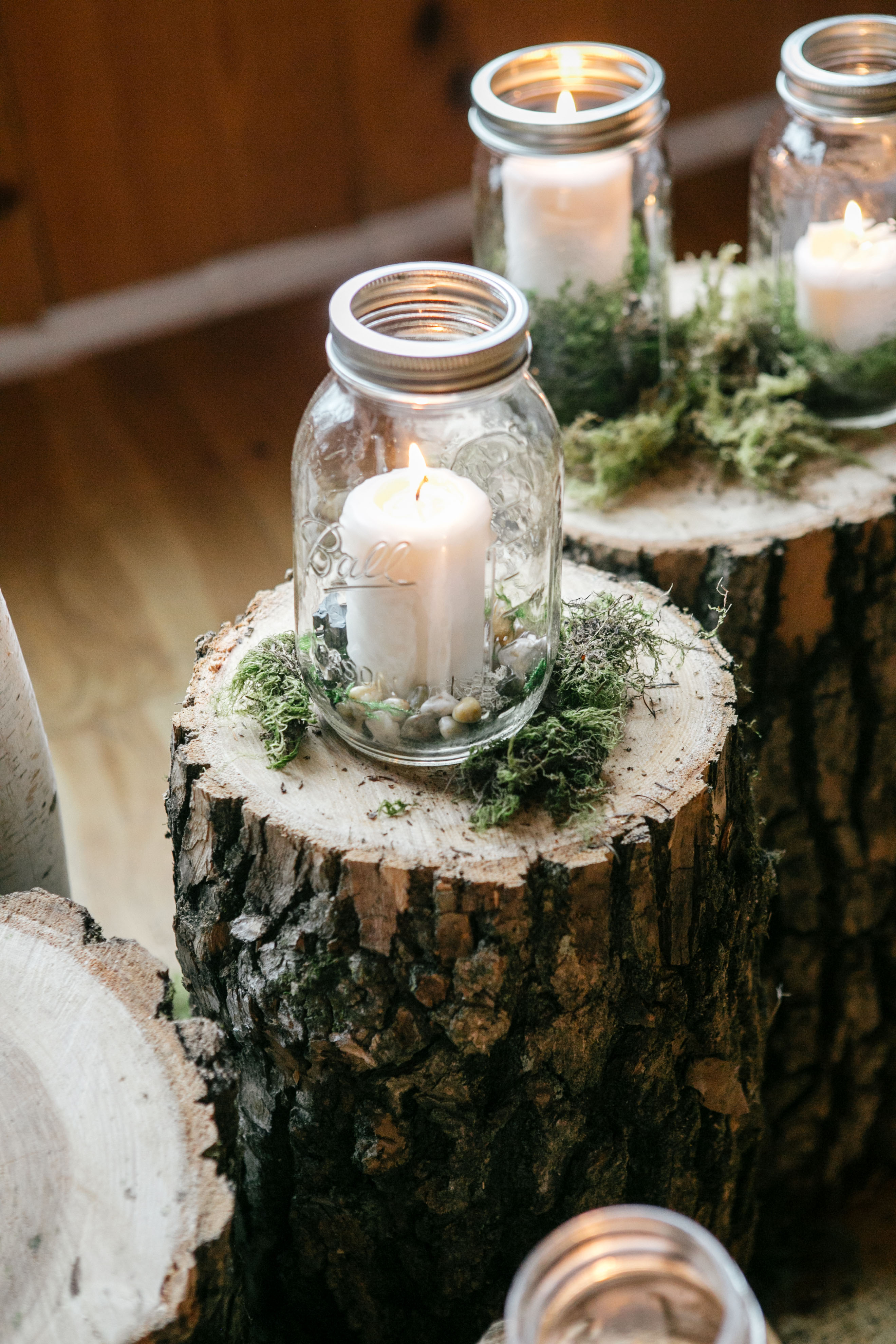 mason jar candle holder over tree stumps