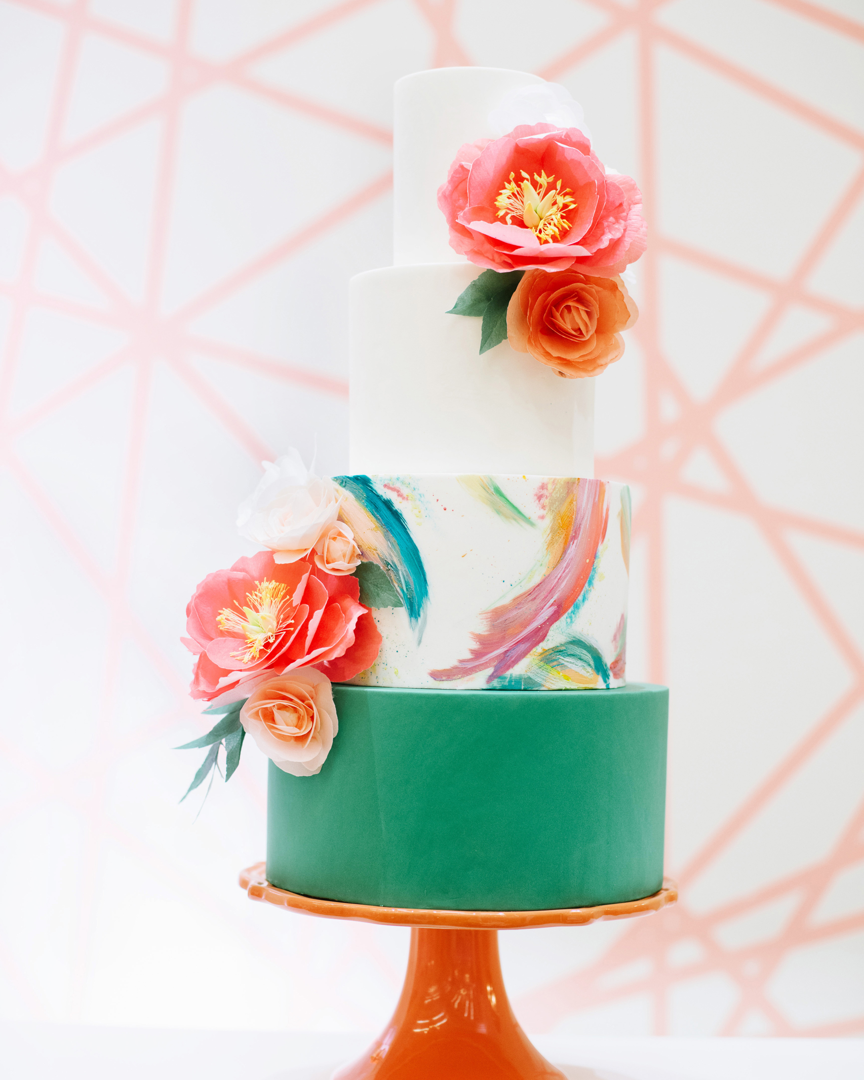 four tiered bottom tier green frosted, third tier multi color brush stroke design and top two white tiers