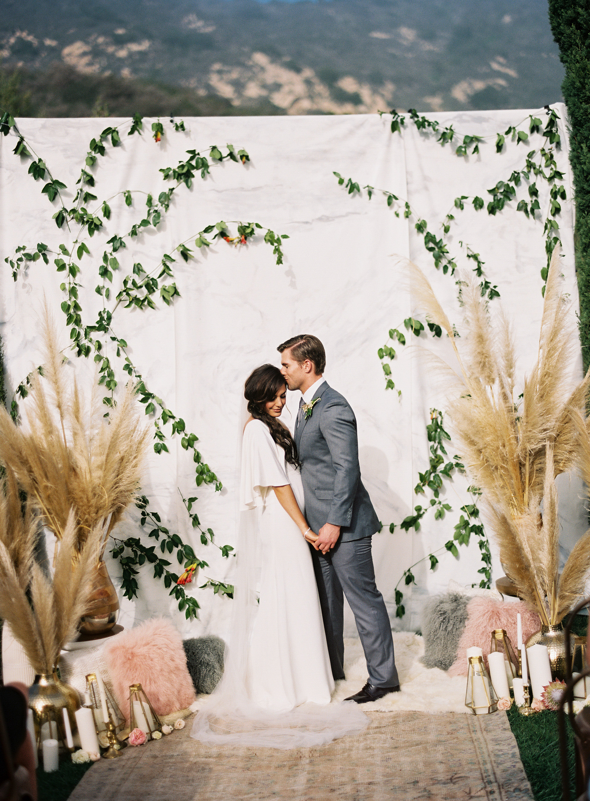 drop cloth backdrop tall pampas grass candles floral arrangement