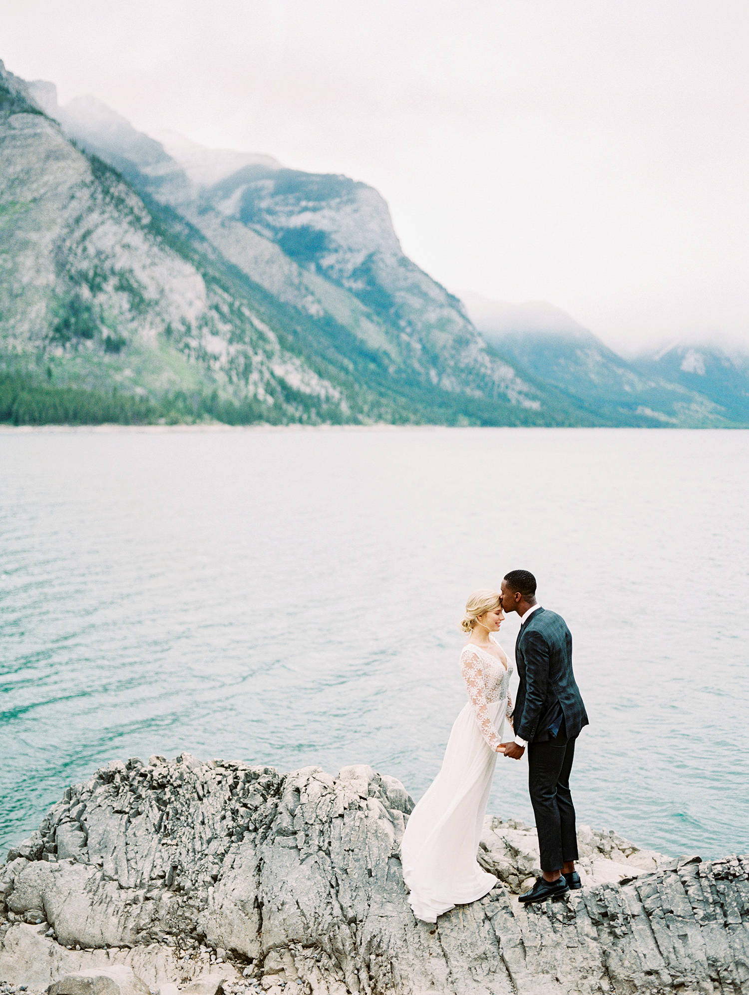 couple standing on rock overlooking water