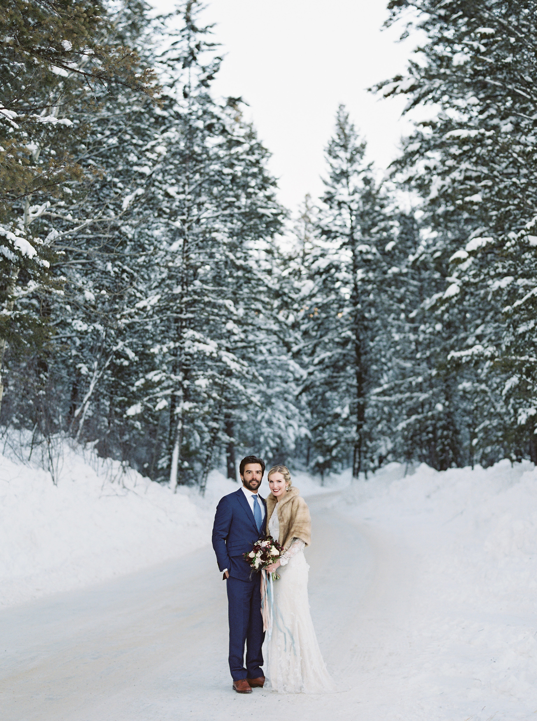 Bride and Groom in front of Evergreens