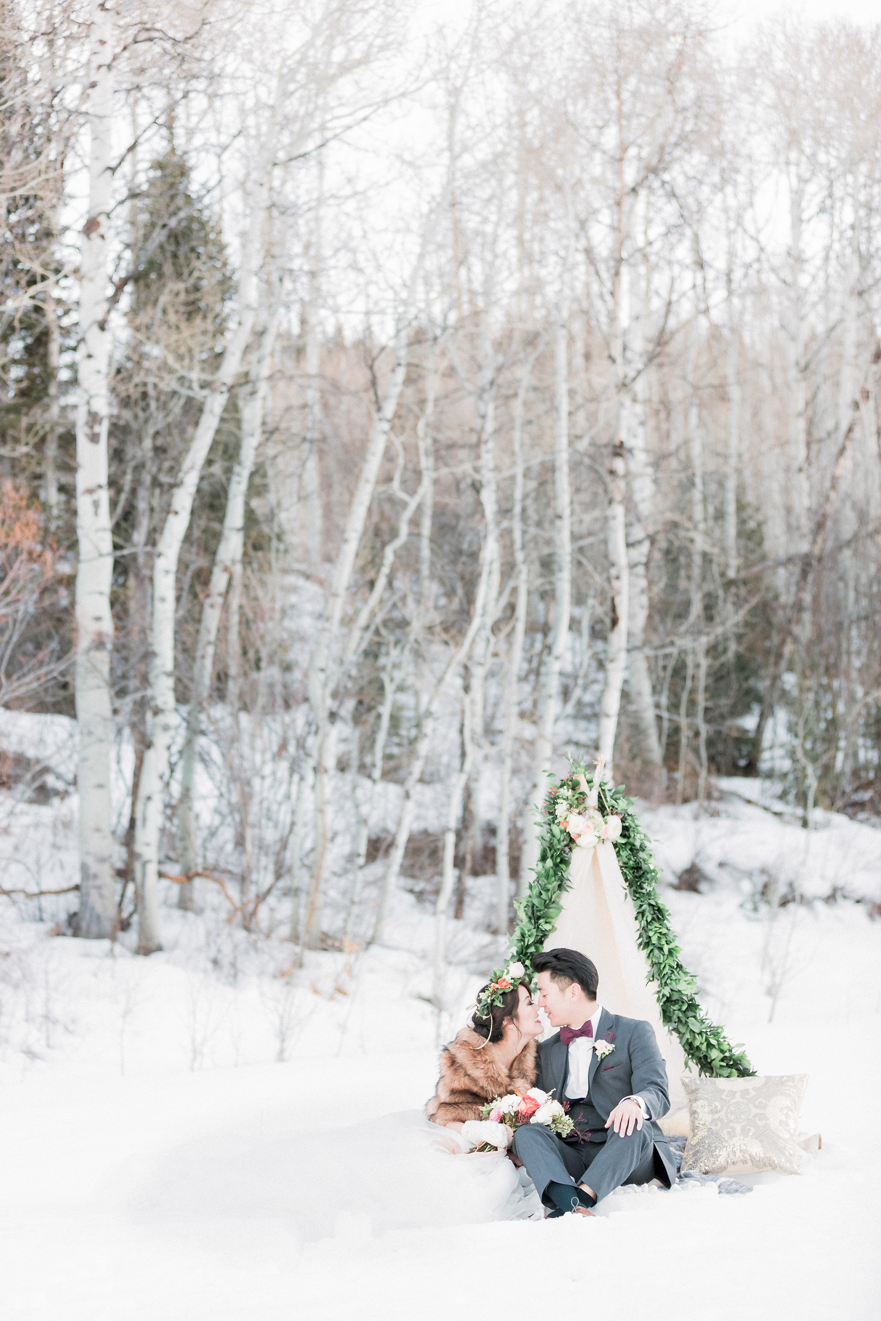 Bride and Groom Sitting in Snow
