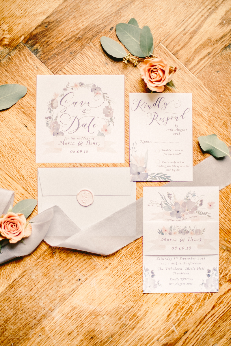off white stationary save the dates with pink and purple floral design