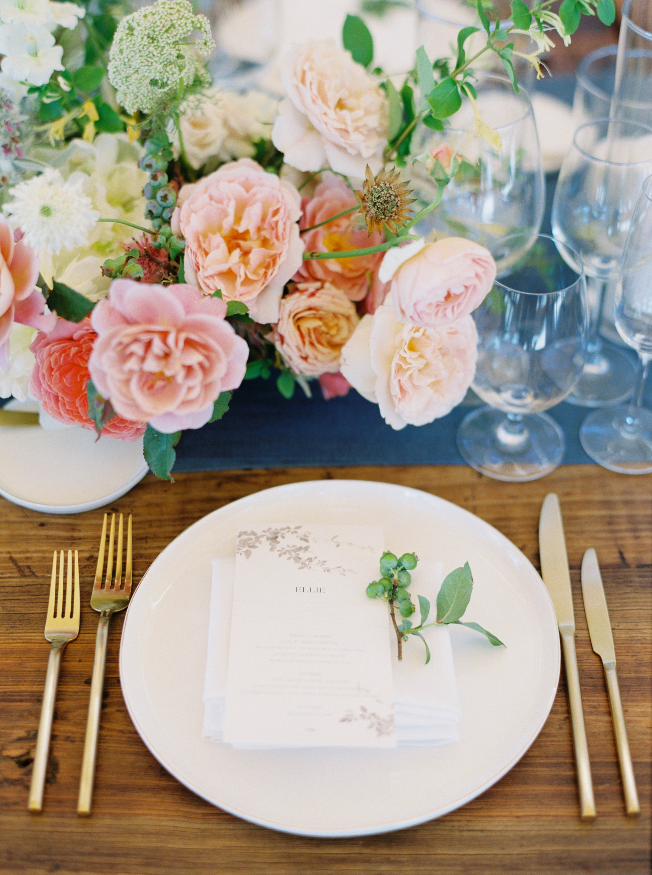 pink and orange centerpiece on blue table runner