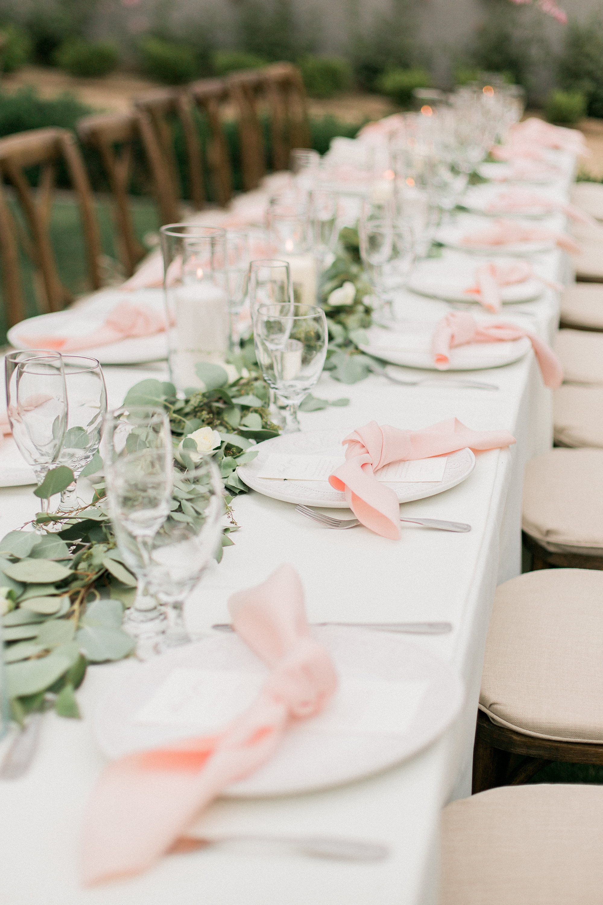 table setting with eucalyptus pink napkins and candles