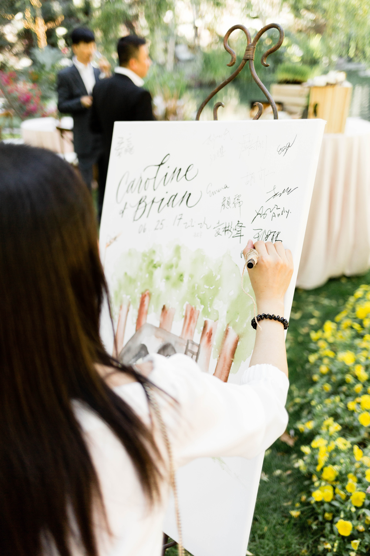 woman signing wedding painting