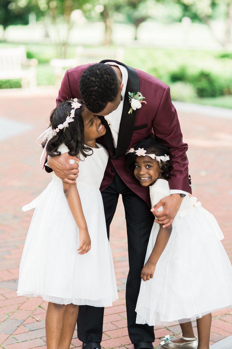 groom hugging two flower girls