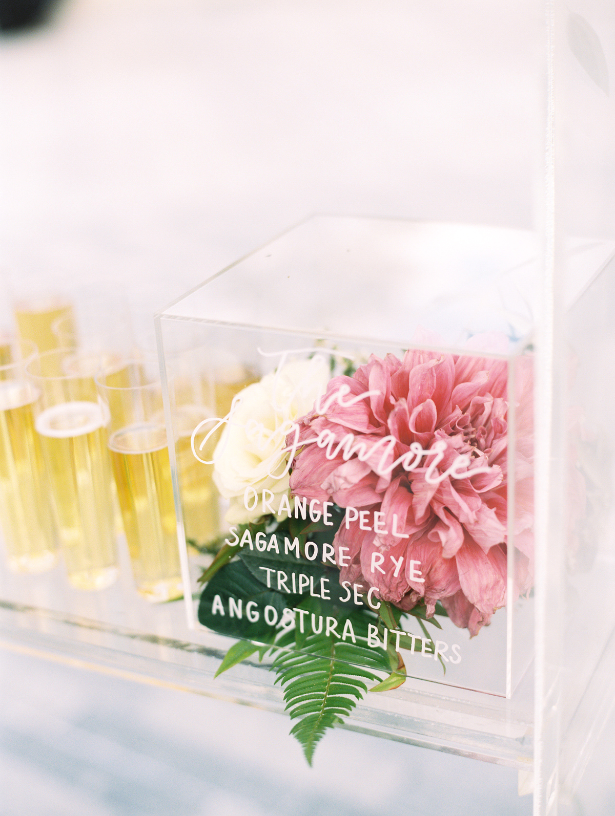 lucite cocktail menu box containing dahlias and roses