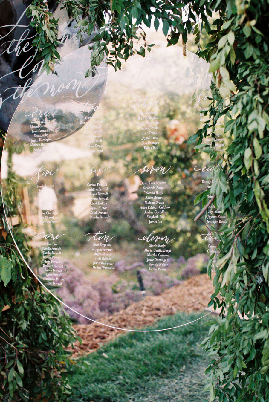 round lucite seating chart displayed with an acrylic moon