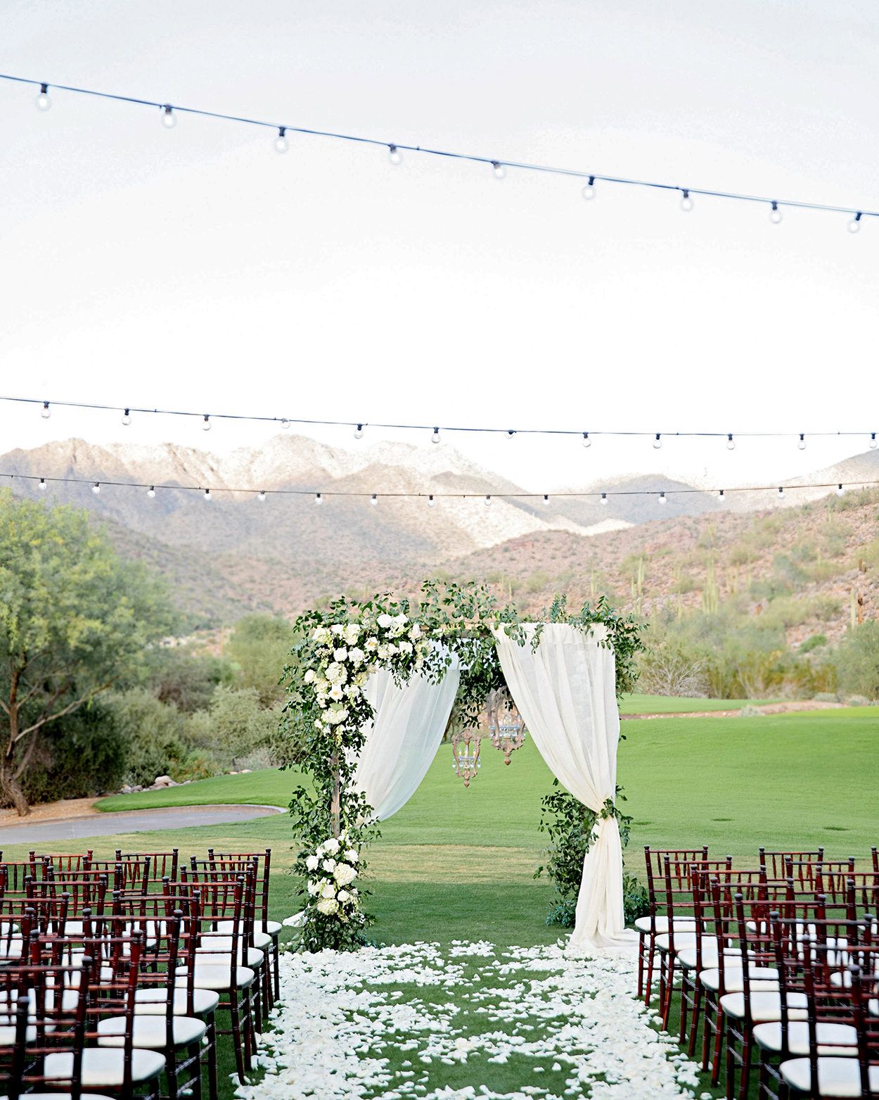 outdoor ceremony arch with tulle and greenery