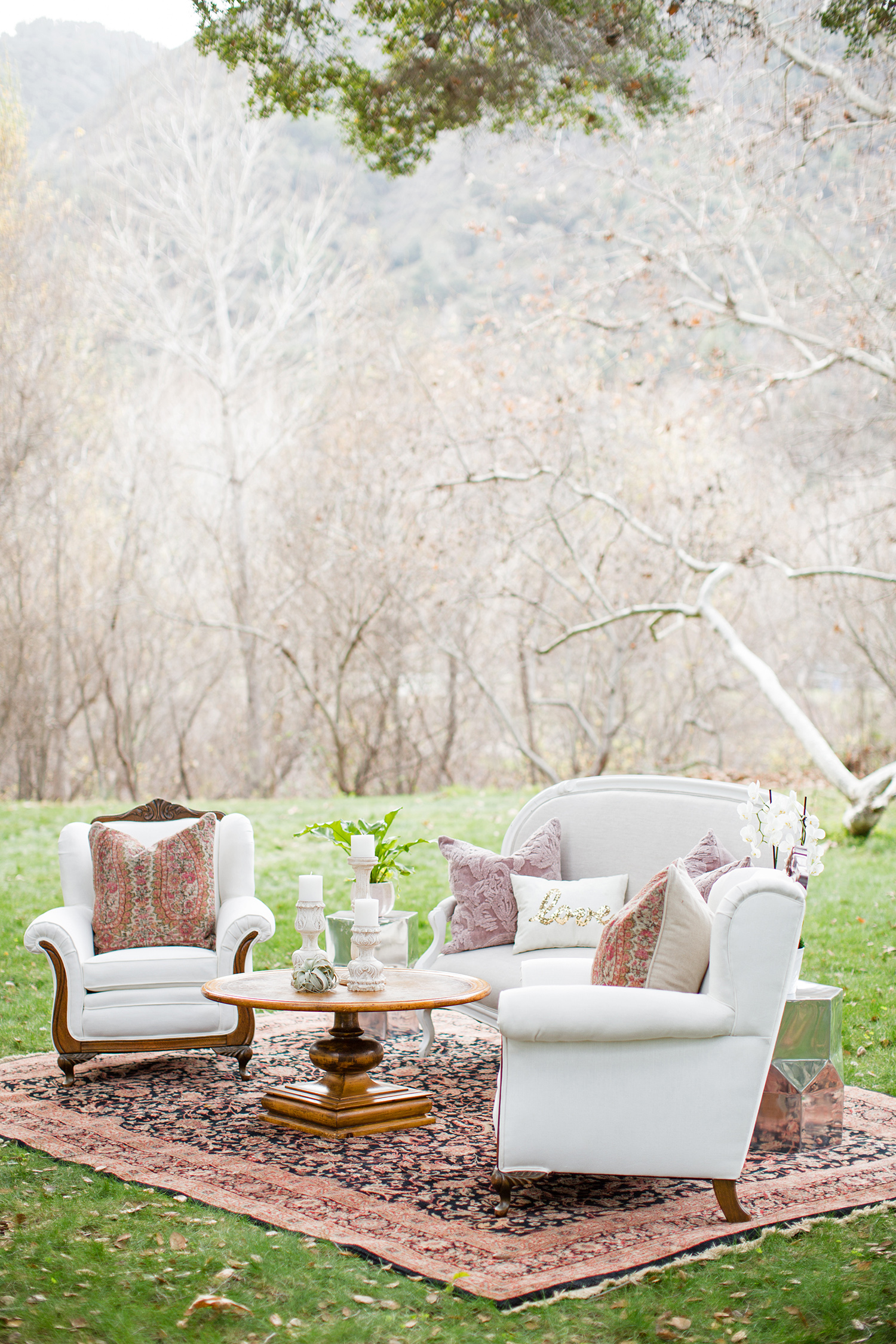 wedding lounge white chairs with bohemian accents in forest