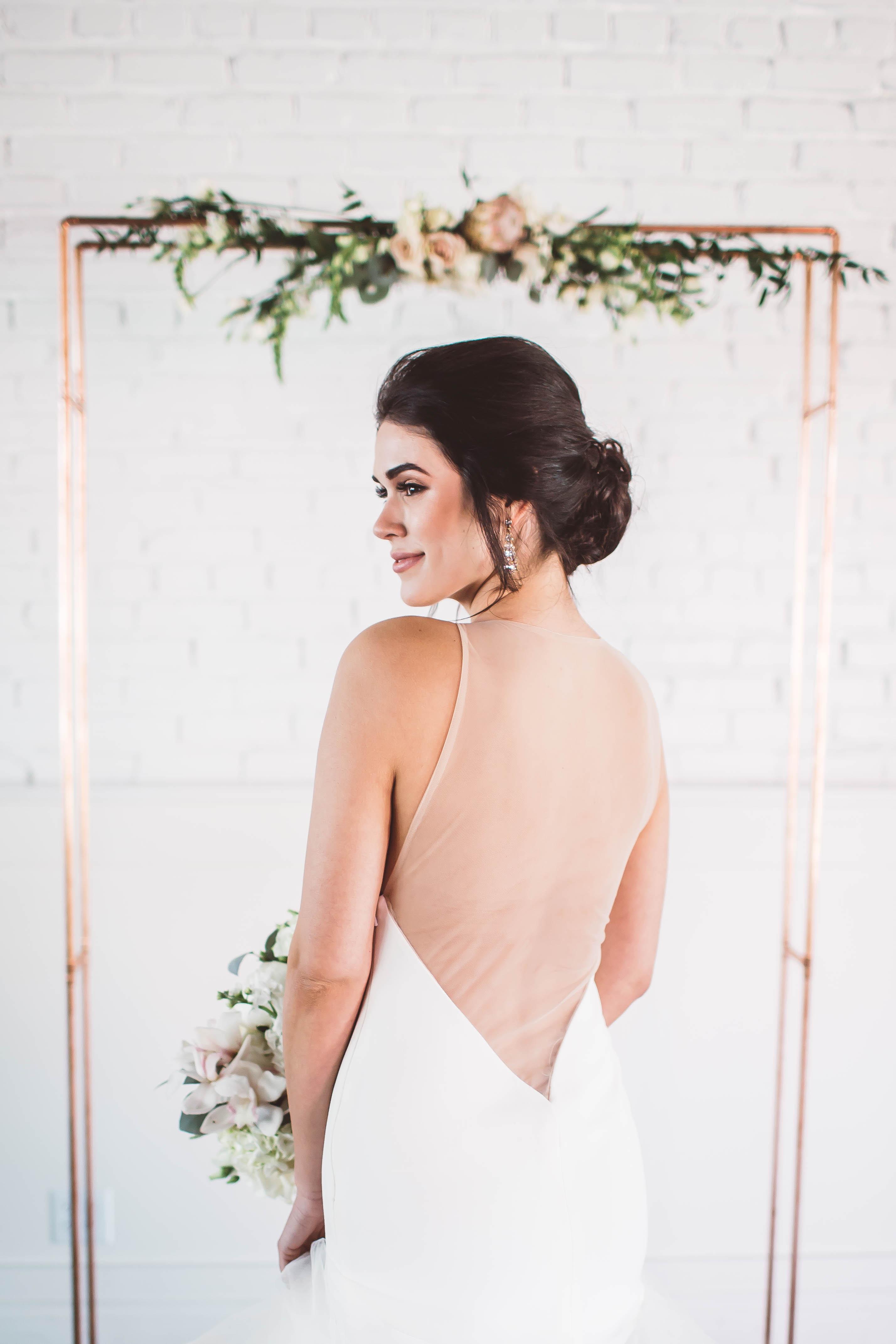 rose gold wedding ideas bride beneath metallic arch