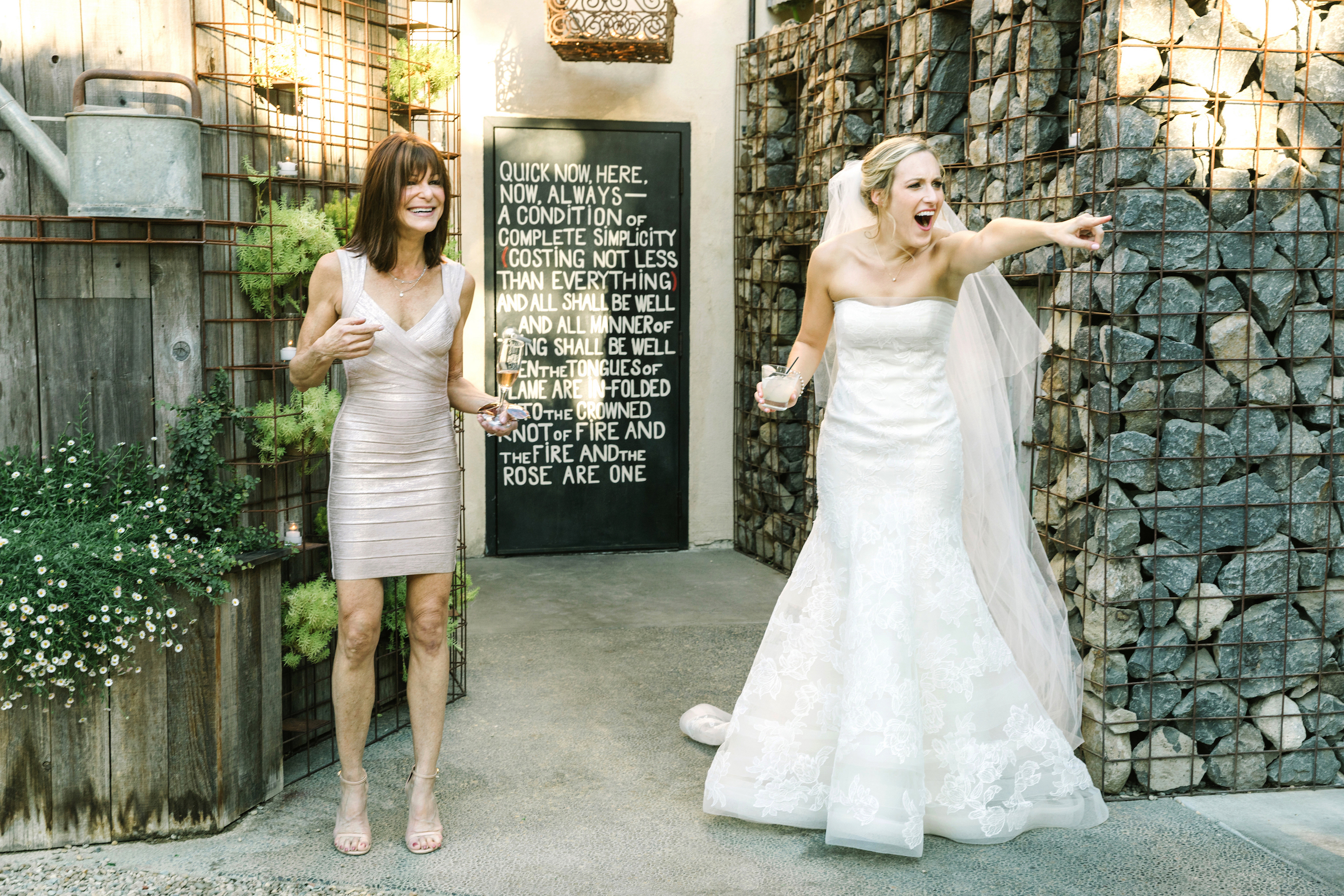 A Bride and Her Mom Holding a Drink on Her Wedding Day