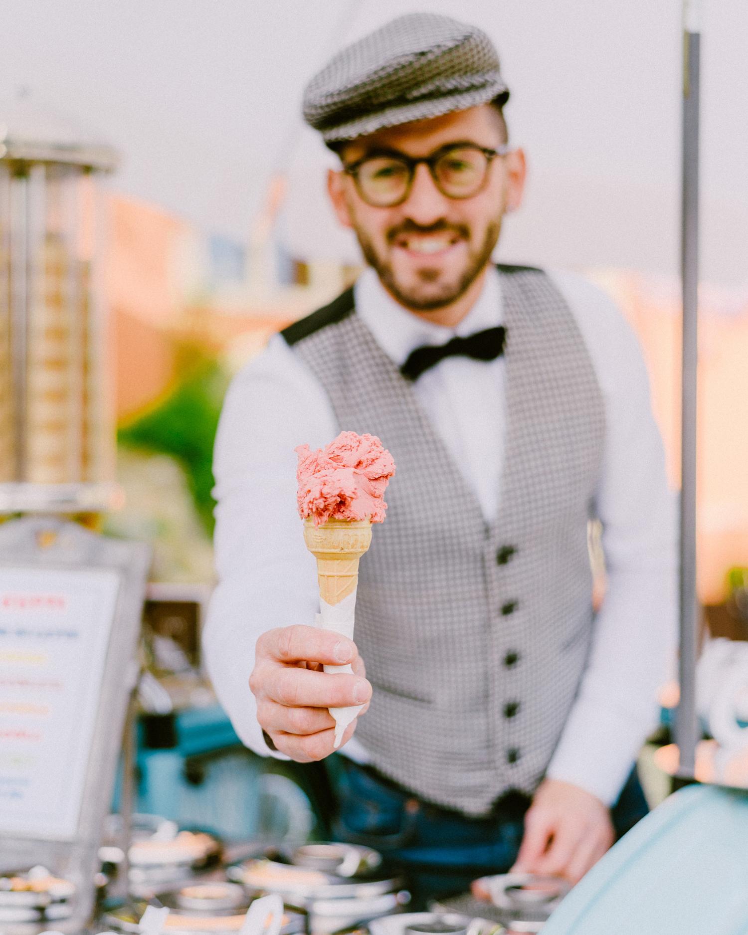man serving pink ice cream cone