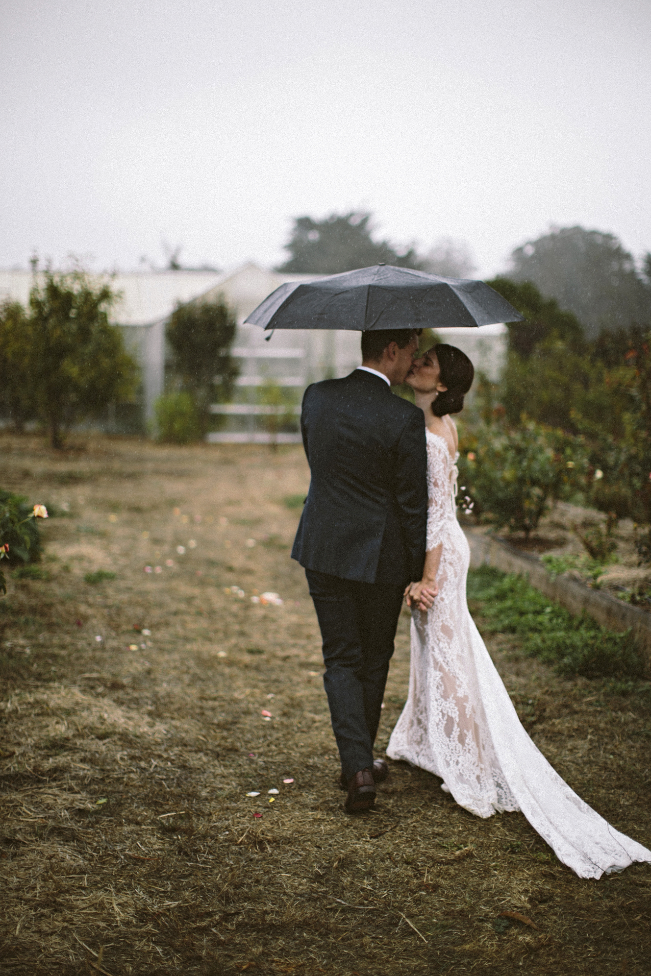 rainy wedding bride and groom kissing with umbrella