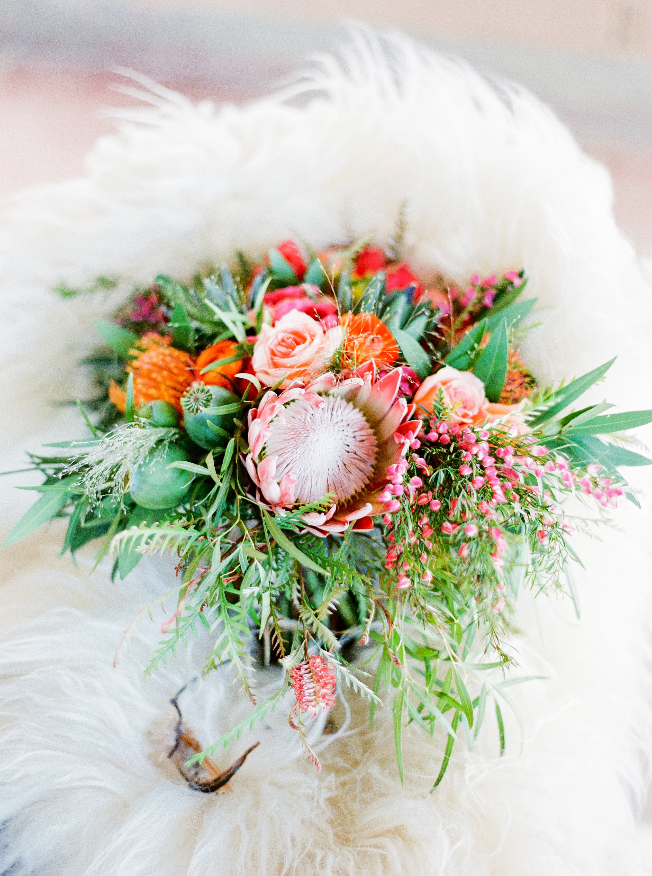 Bright peach and pink king protea wedding bouquet