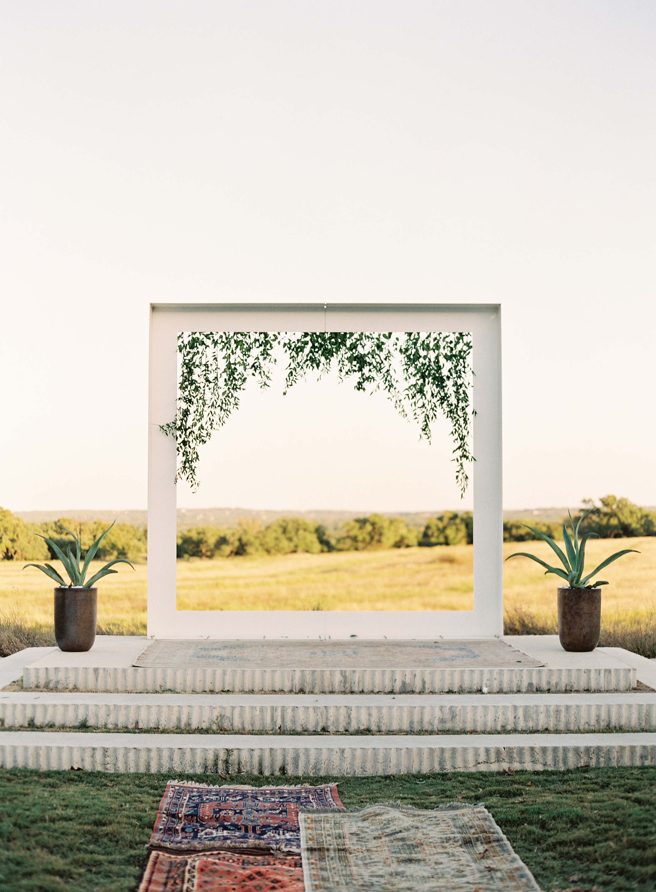 Outdoor altar white wood frame greenery hanging