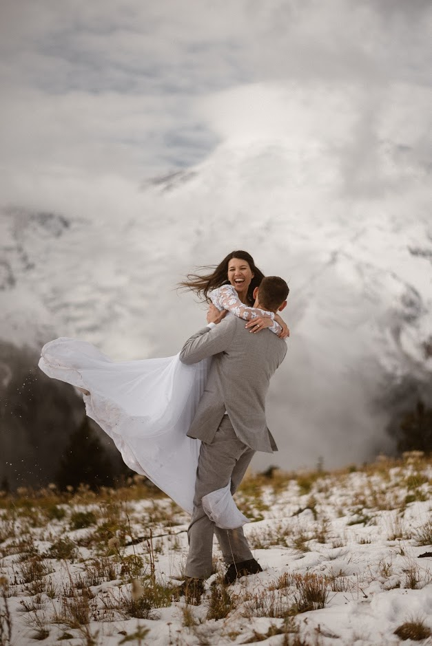 groom carrying bride in snow