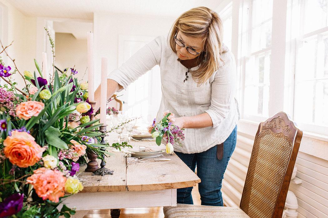 Holly Heider arranging floral centerpiece
