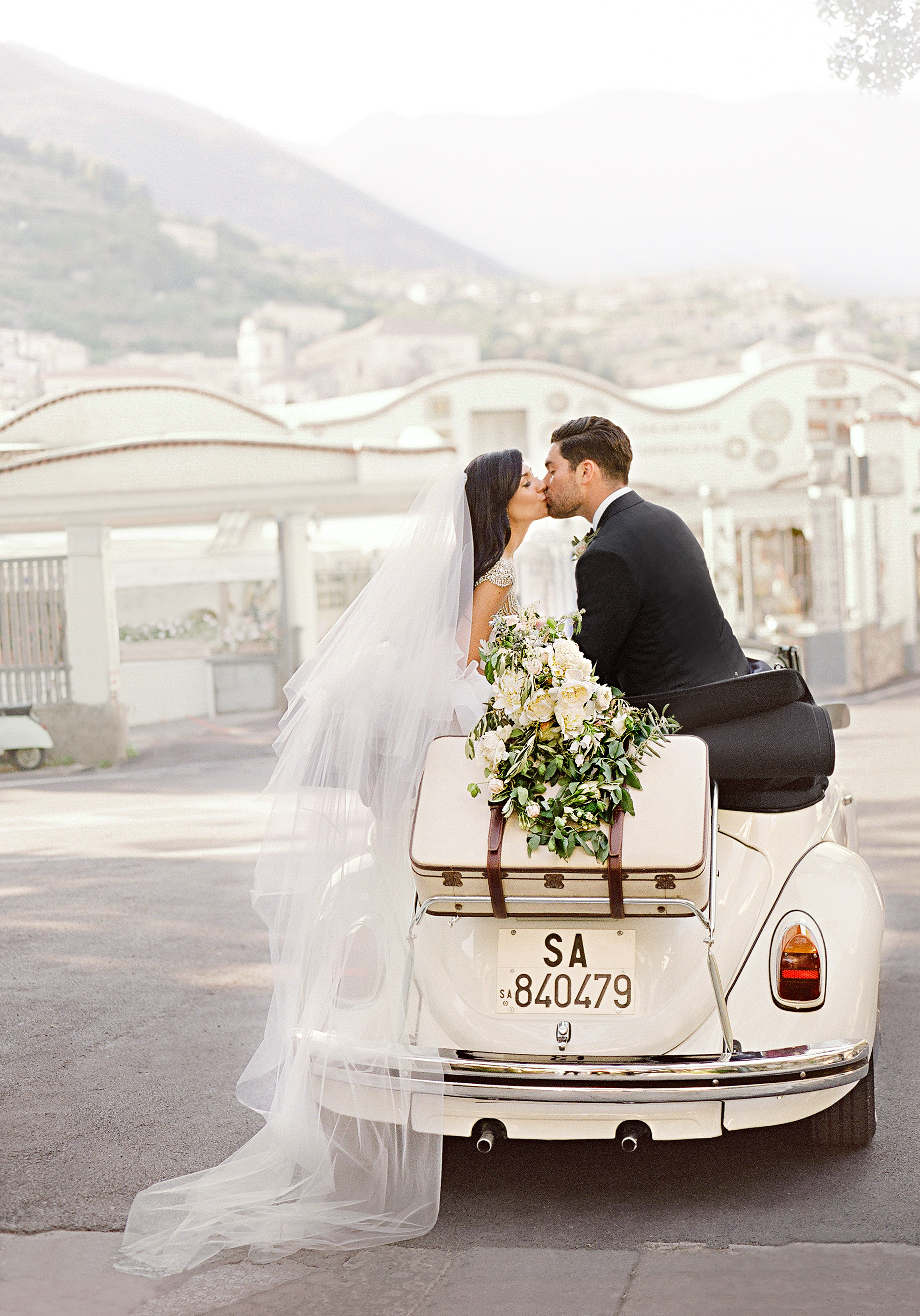 married couple sitting in the back of white car kissing