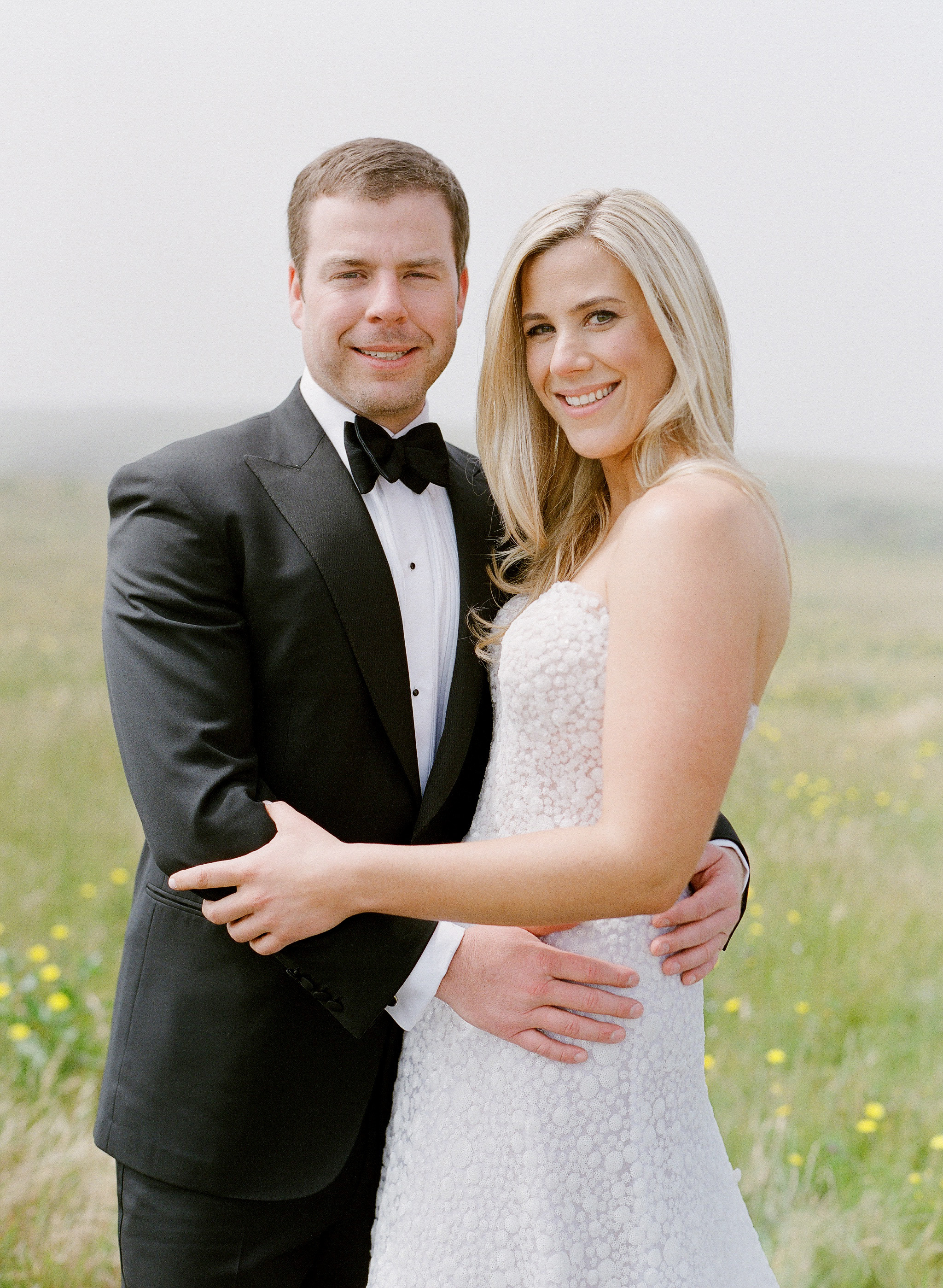 whitney zach wedding couple embracing in field
