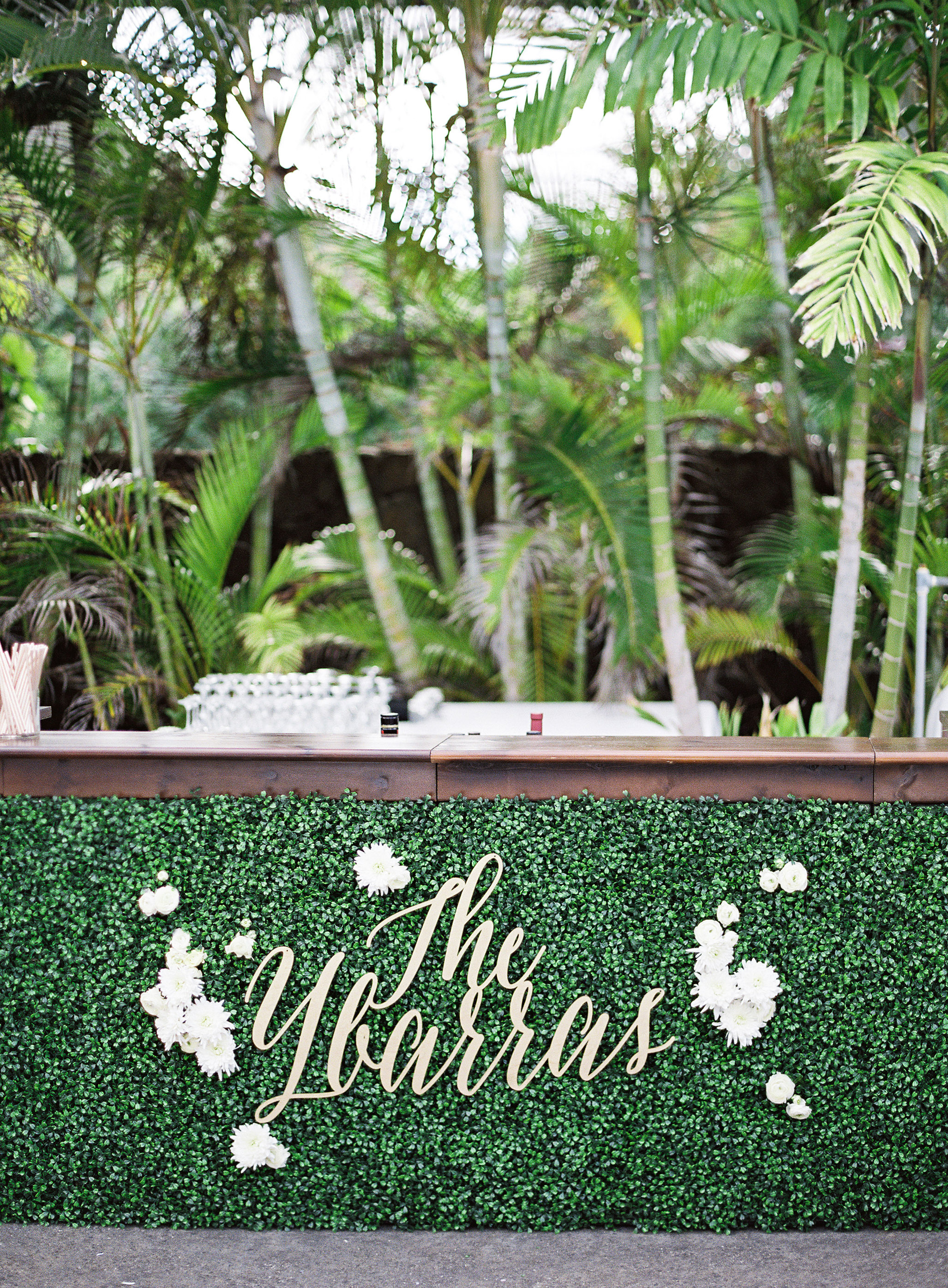wedding decor name lettering on bar green palm trees