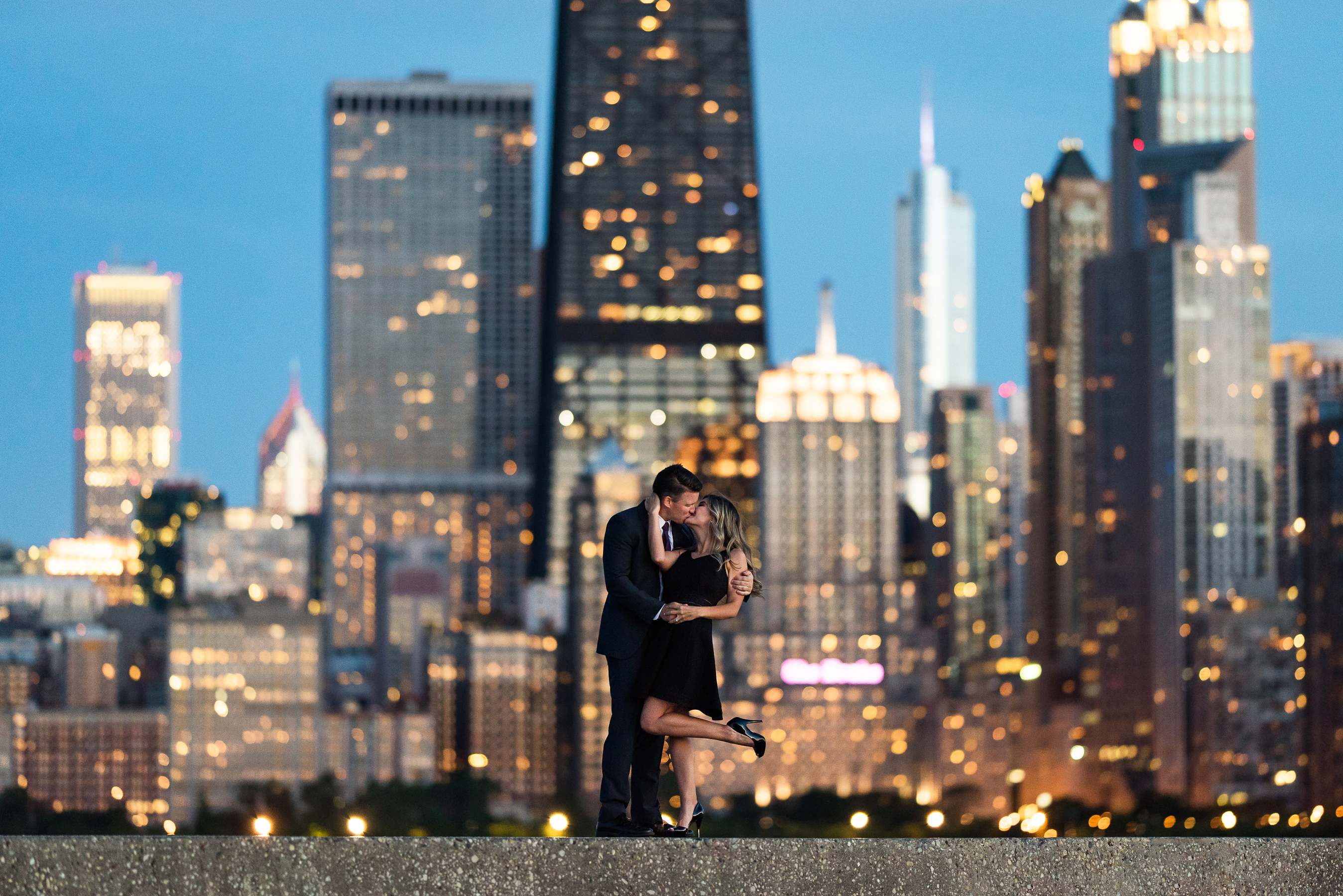 couple kissing by city skyline outdoor engagement photos