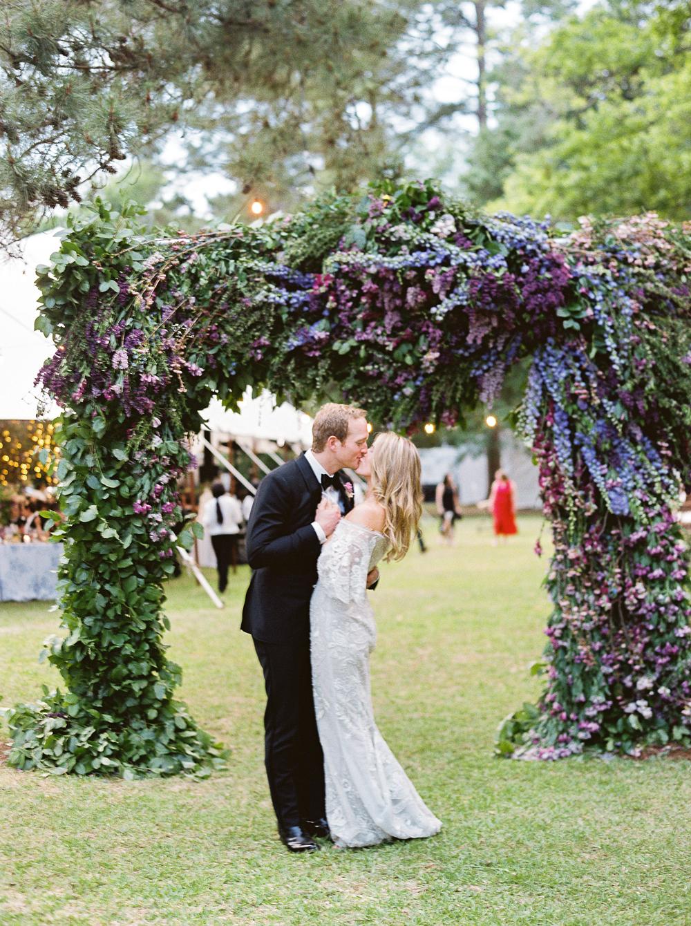 julia mitchell wedding couple kissing beneath arch