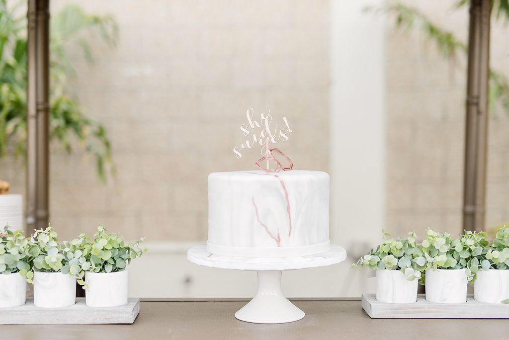 marbled cake with custom topper next to plants