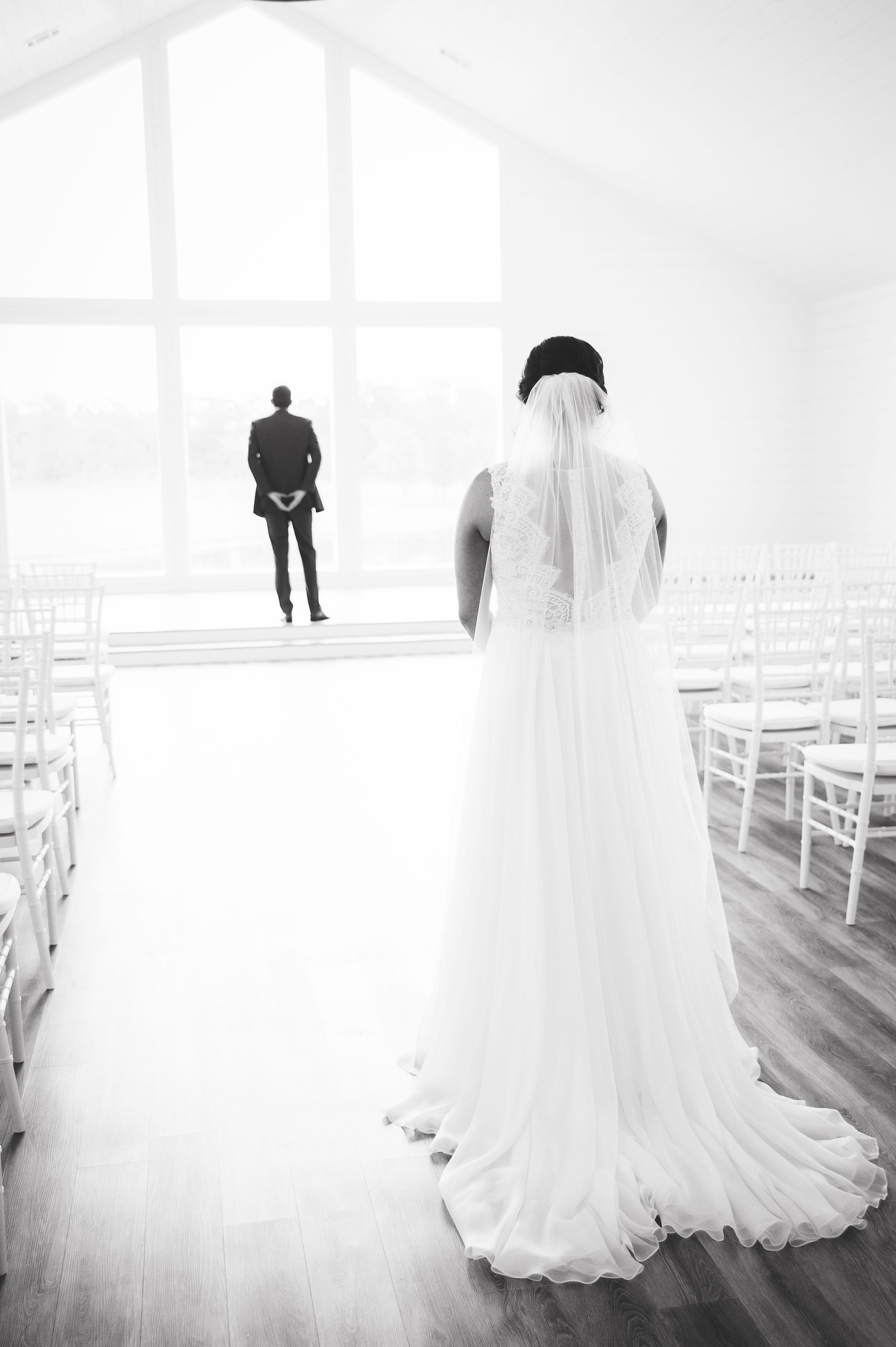 first look photos rachel driskell white room groom waiting bride behind