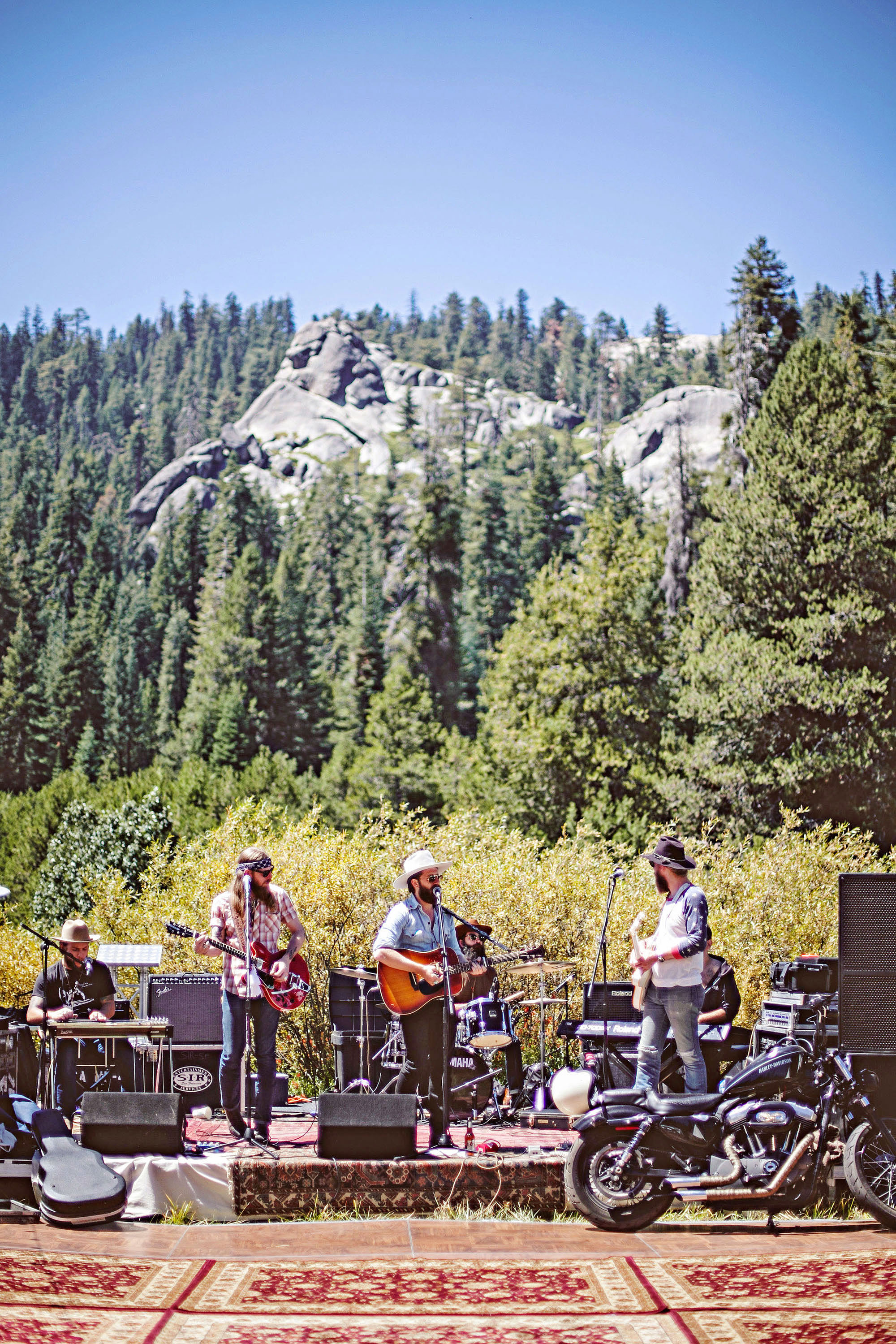 wedding band in front of woods and mountains