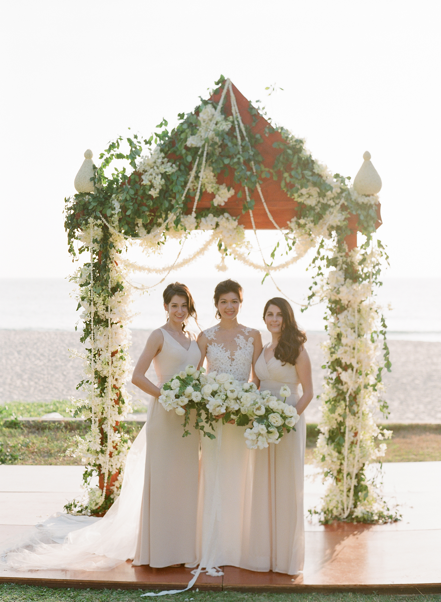 stacy brad wedding thailand bridesmaids under arch on the beach