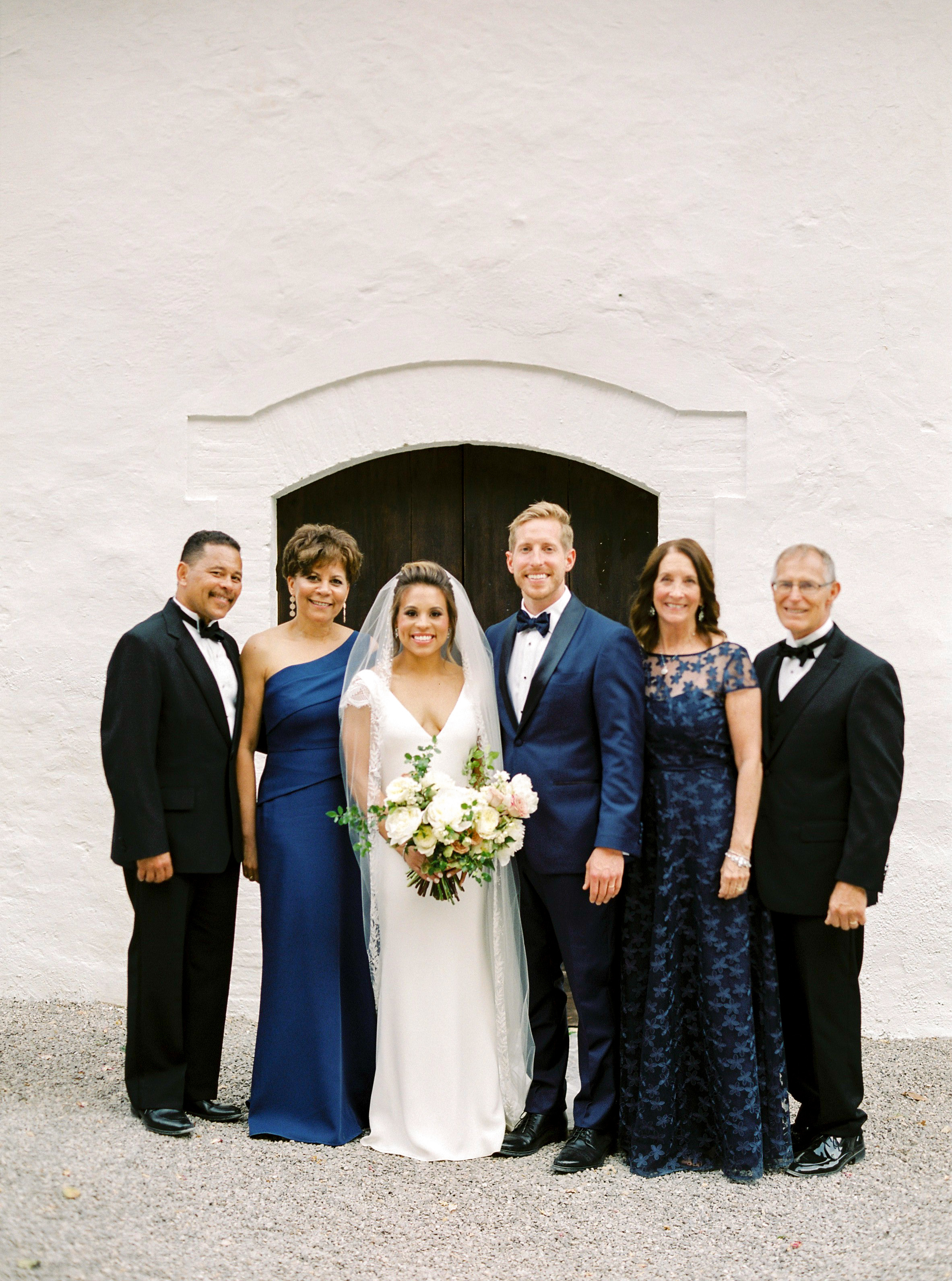 bride and groom pose with parents mother in navy dresses
