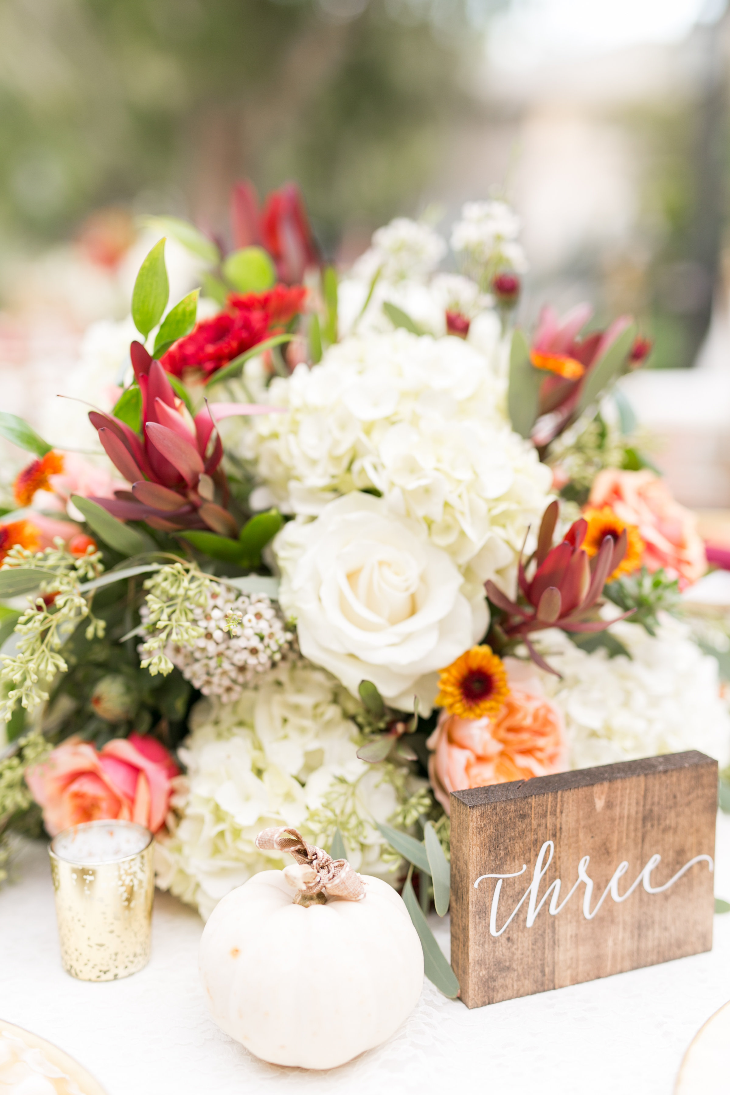 Fall-Hued Centerpiece with White and Red Flowers and Pumpkin Accent