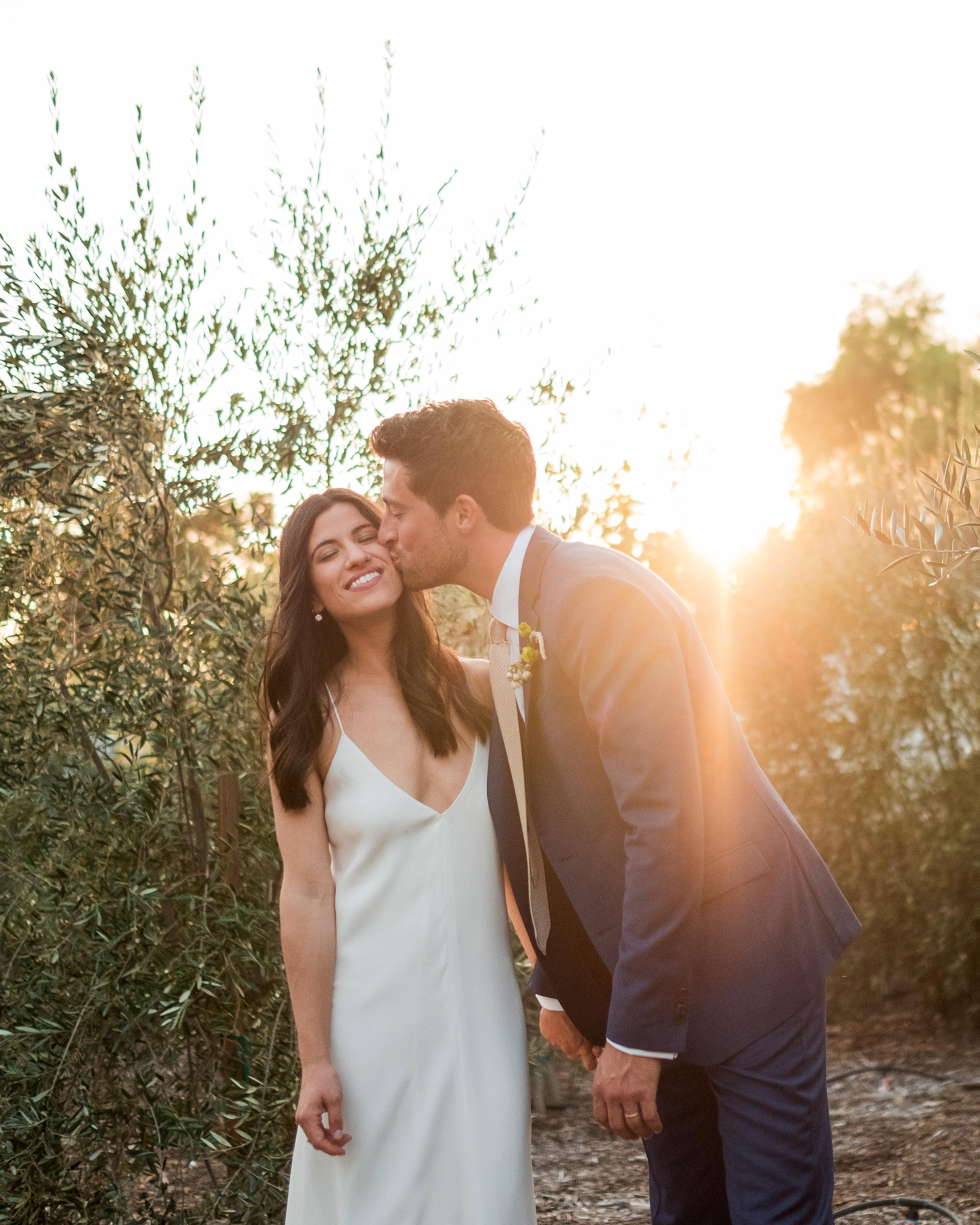 anika max wedding couple cheek kiss sunset