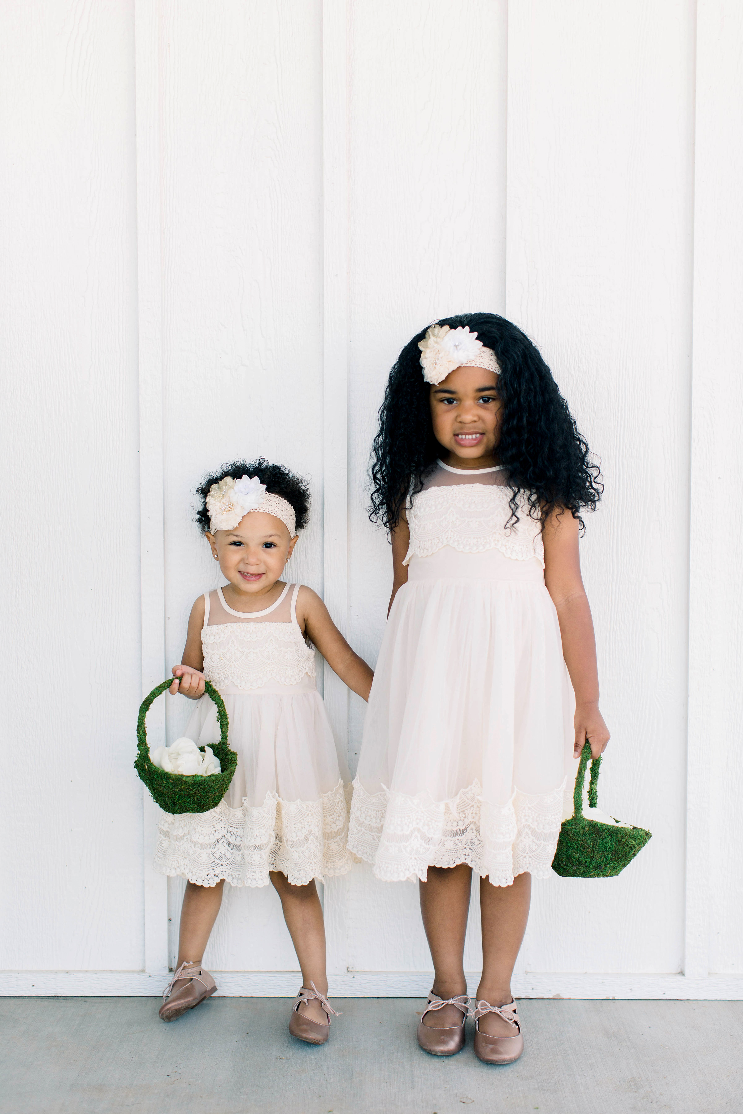 wedding flower girls carrying green baskets