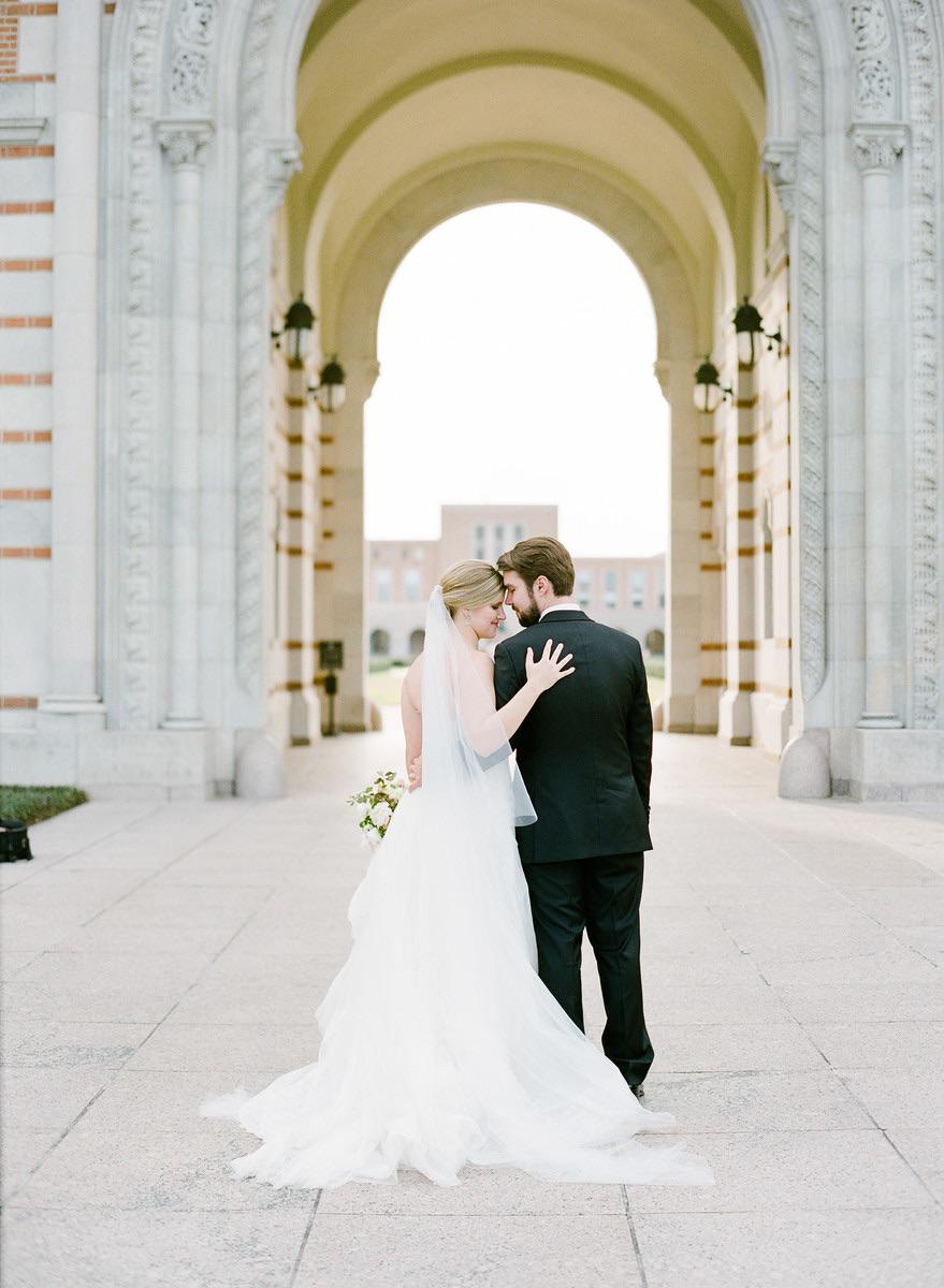 city hall wedding bride embracing groom beneath building arch
