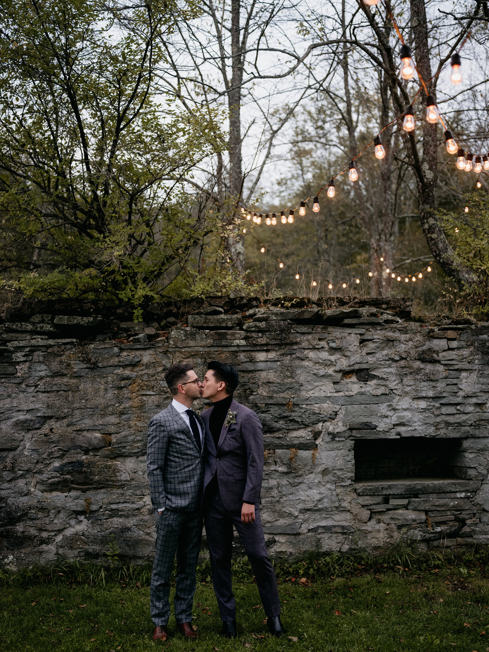 eric eryc wedding grooms in front of stone wall