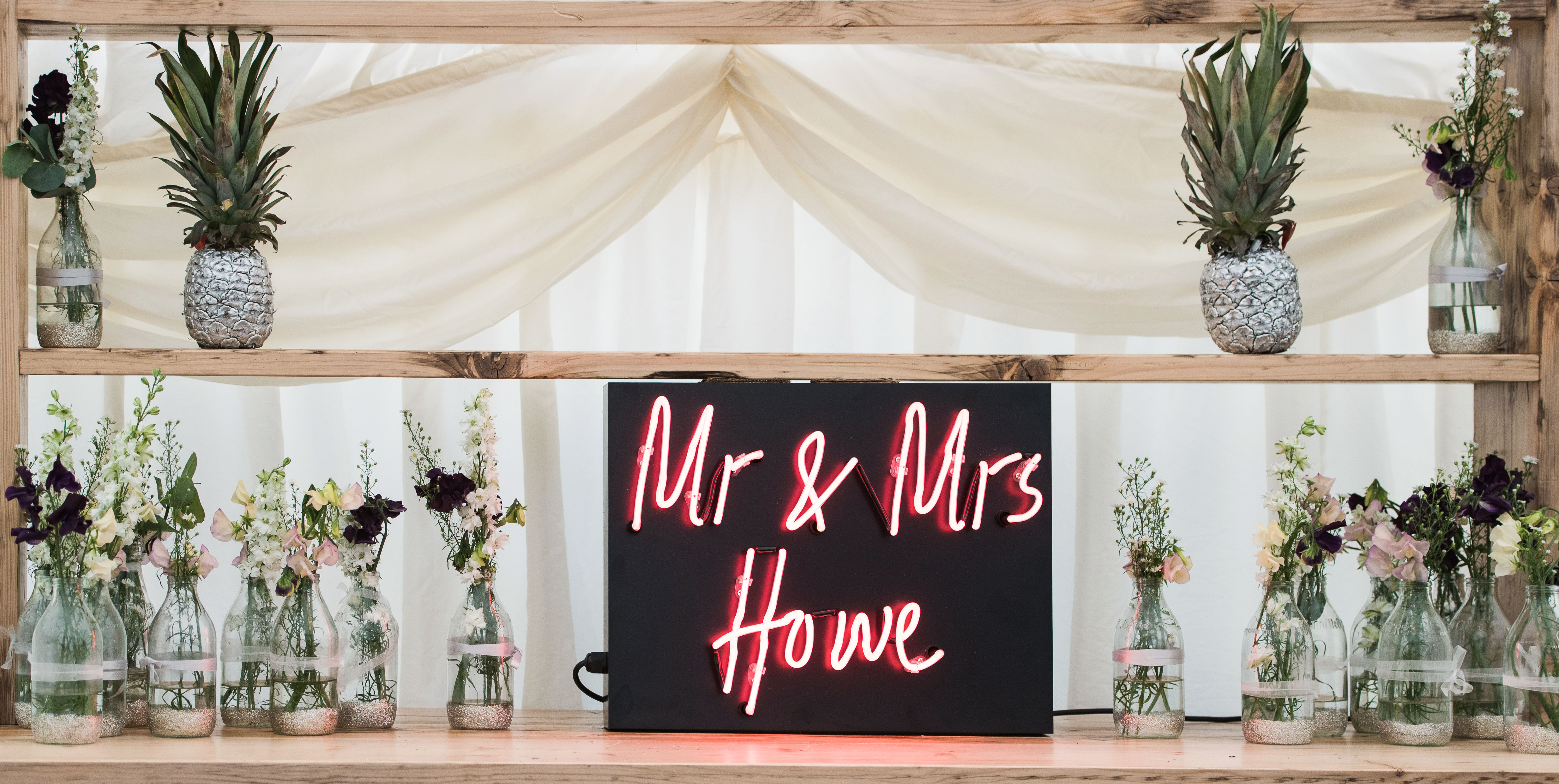 mr and mrs neon sign with pineapples and flowers in jars