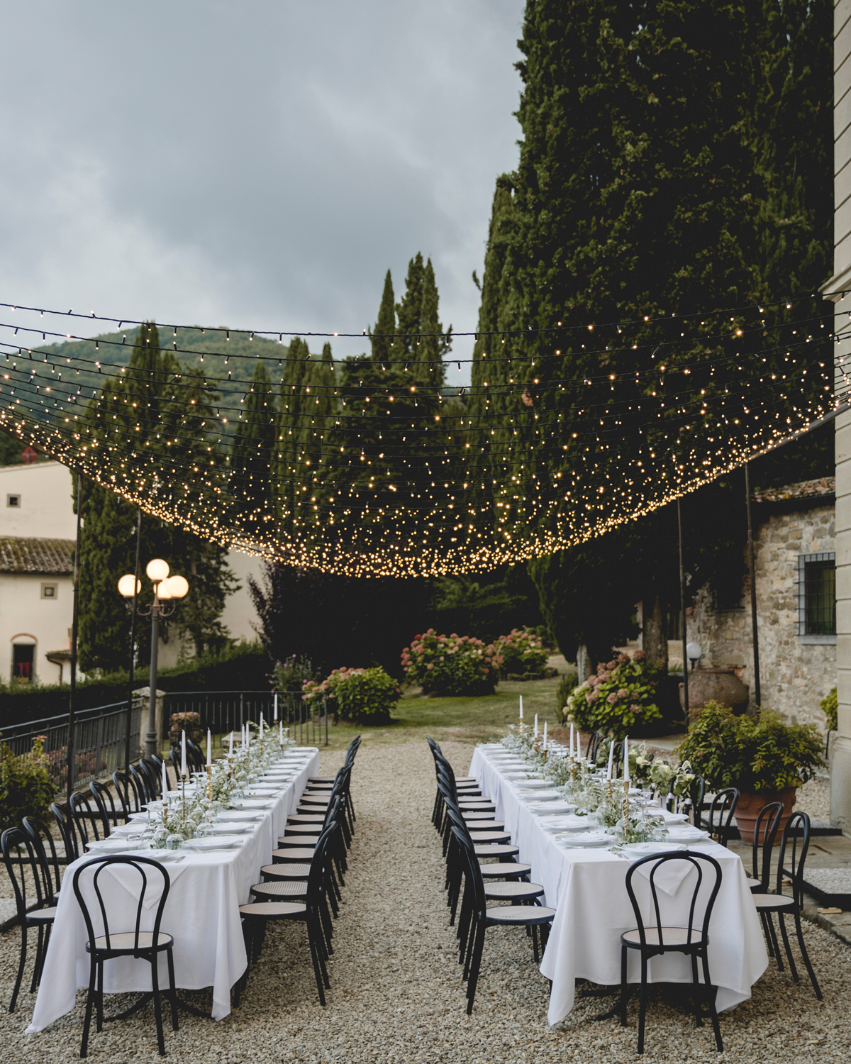 twinkle lights canopy over reception tables in italian courtyard