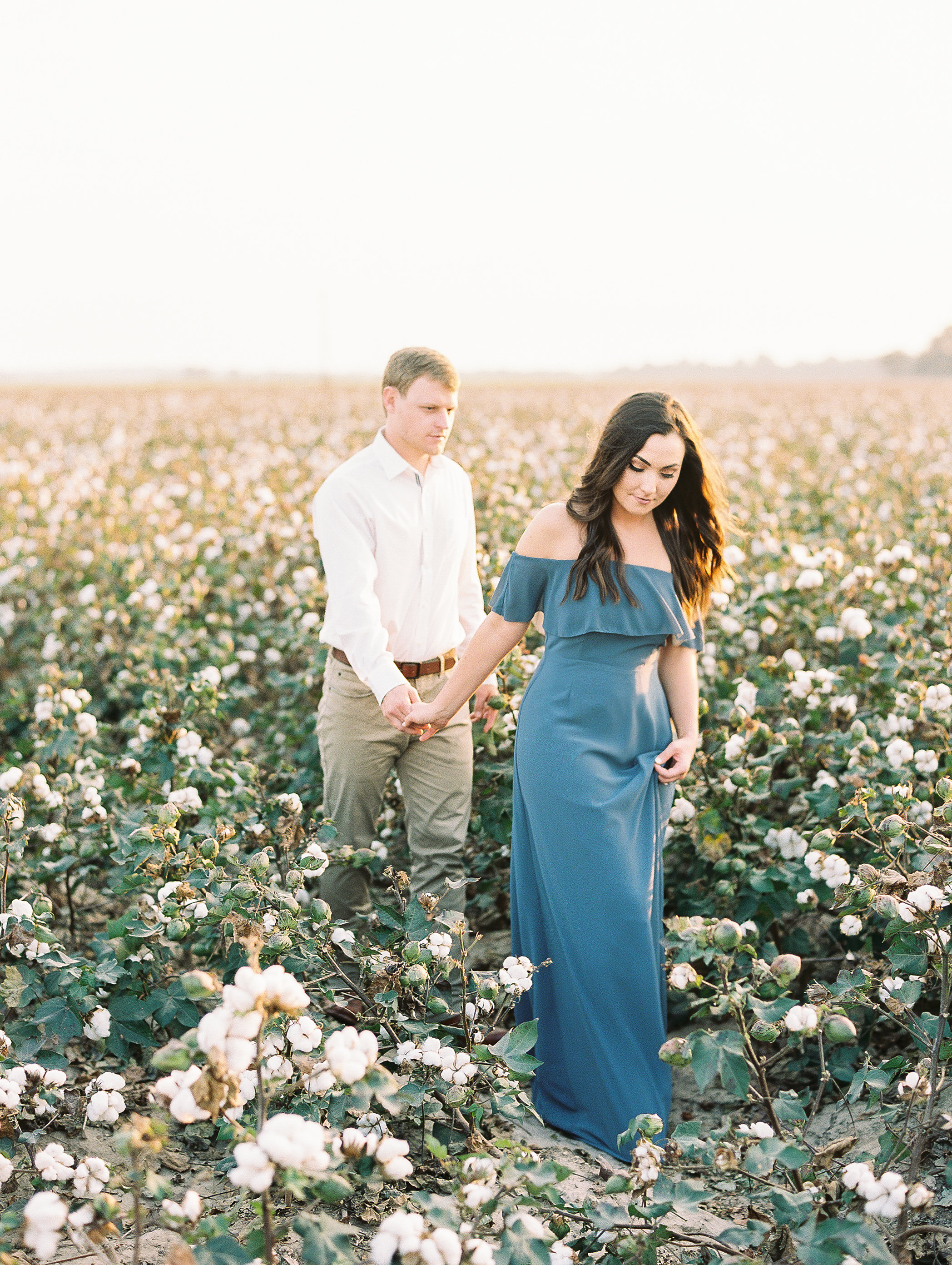 couple walking in cotton field engagement