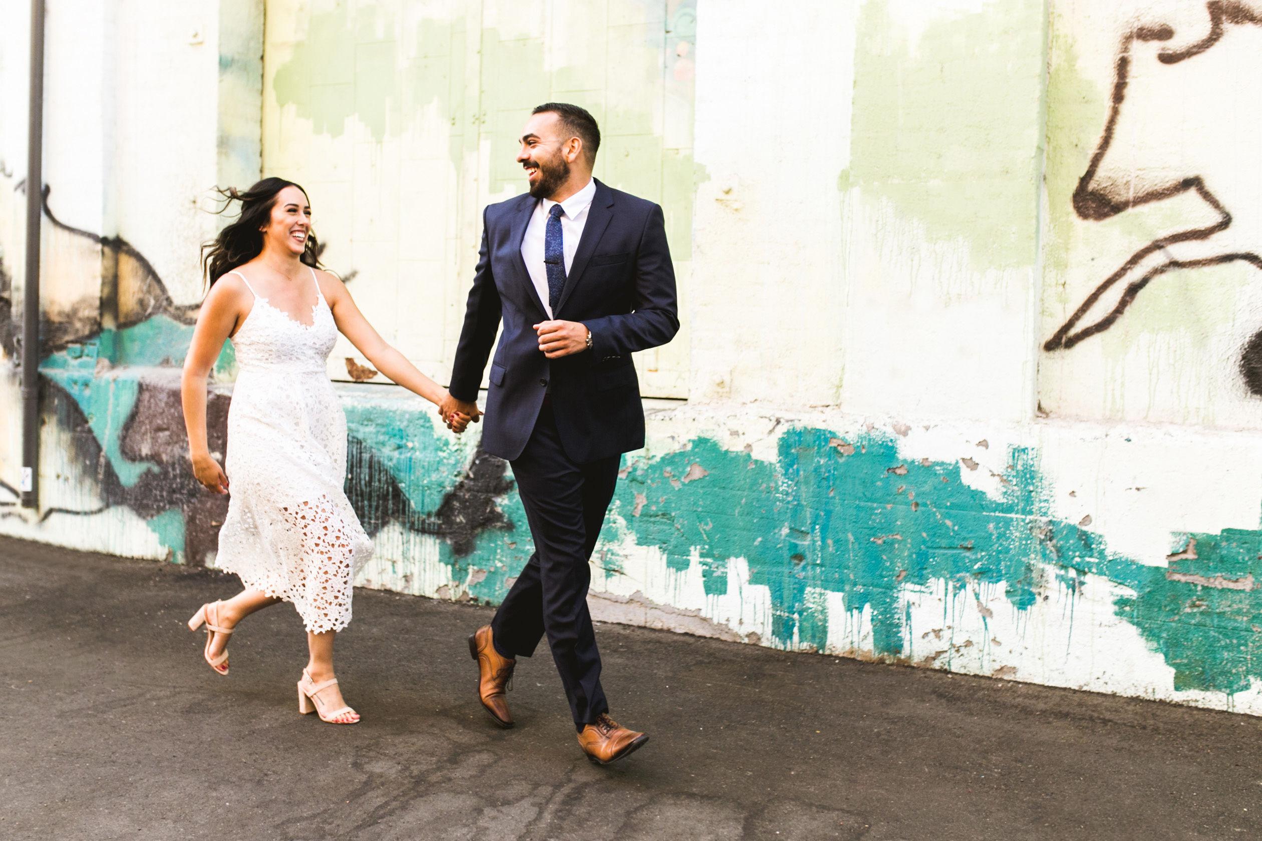 couple running on boardwalk engagement photo