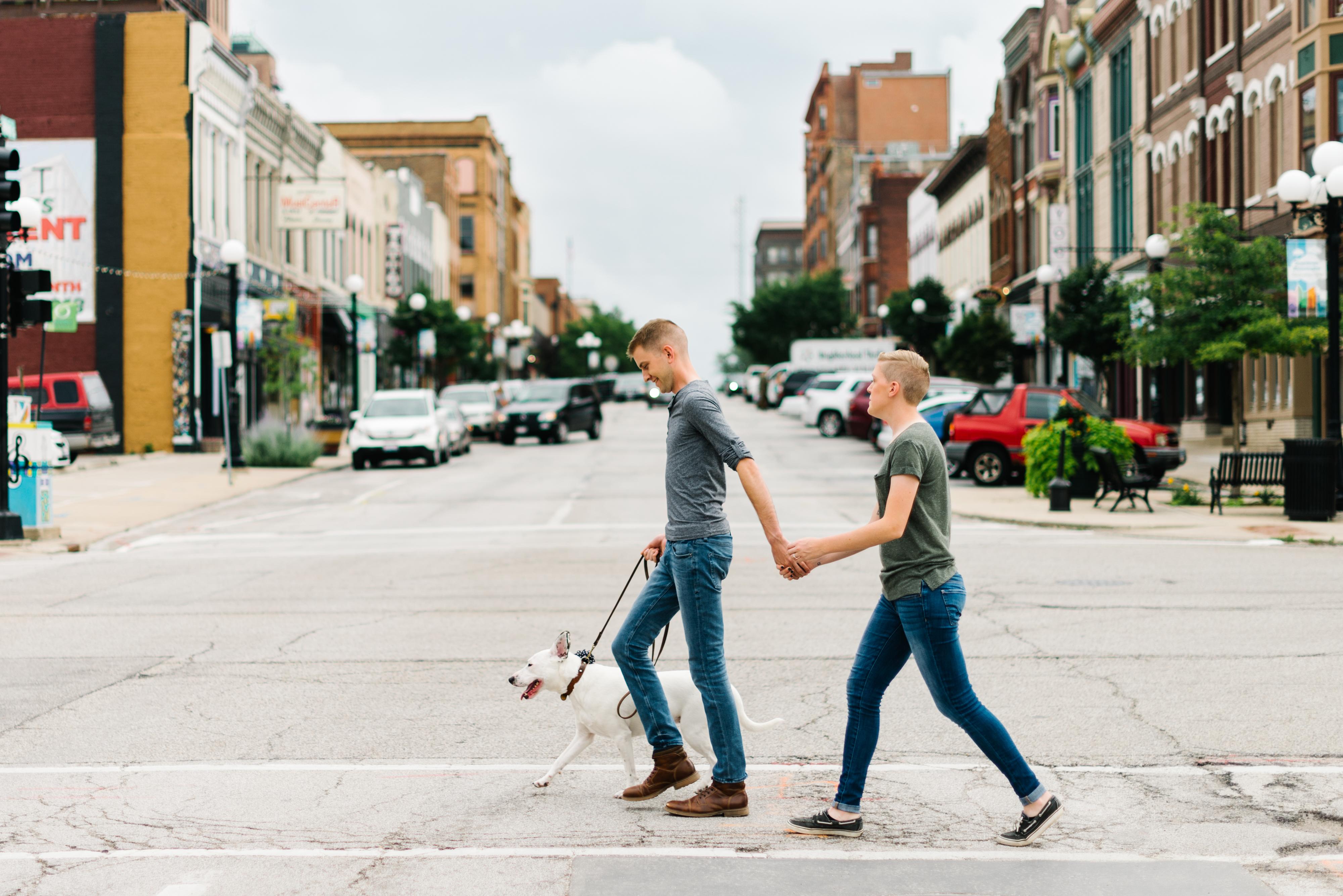 couple walking street with dog engagement photo