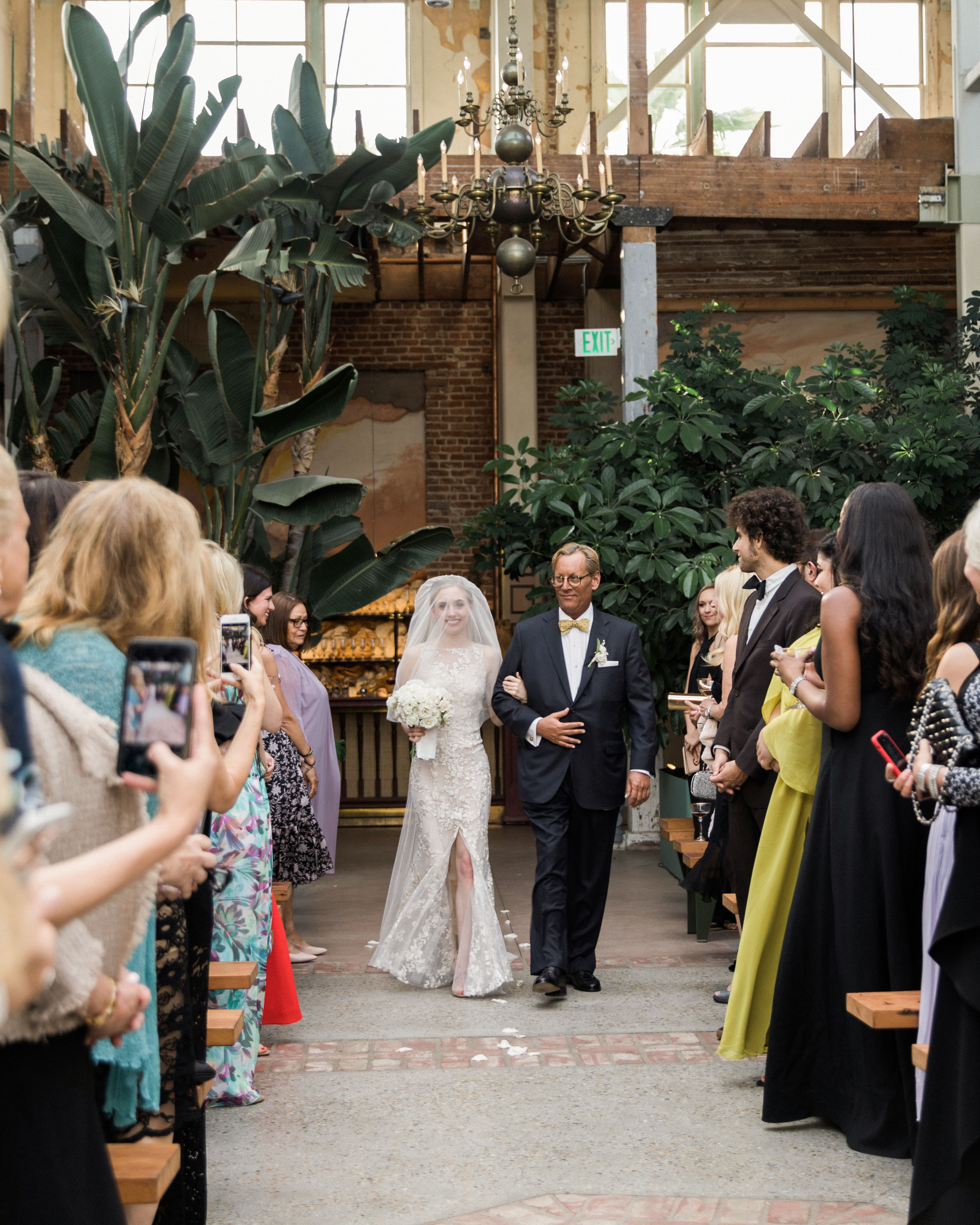 wedding processional bride father guests watching with phones