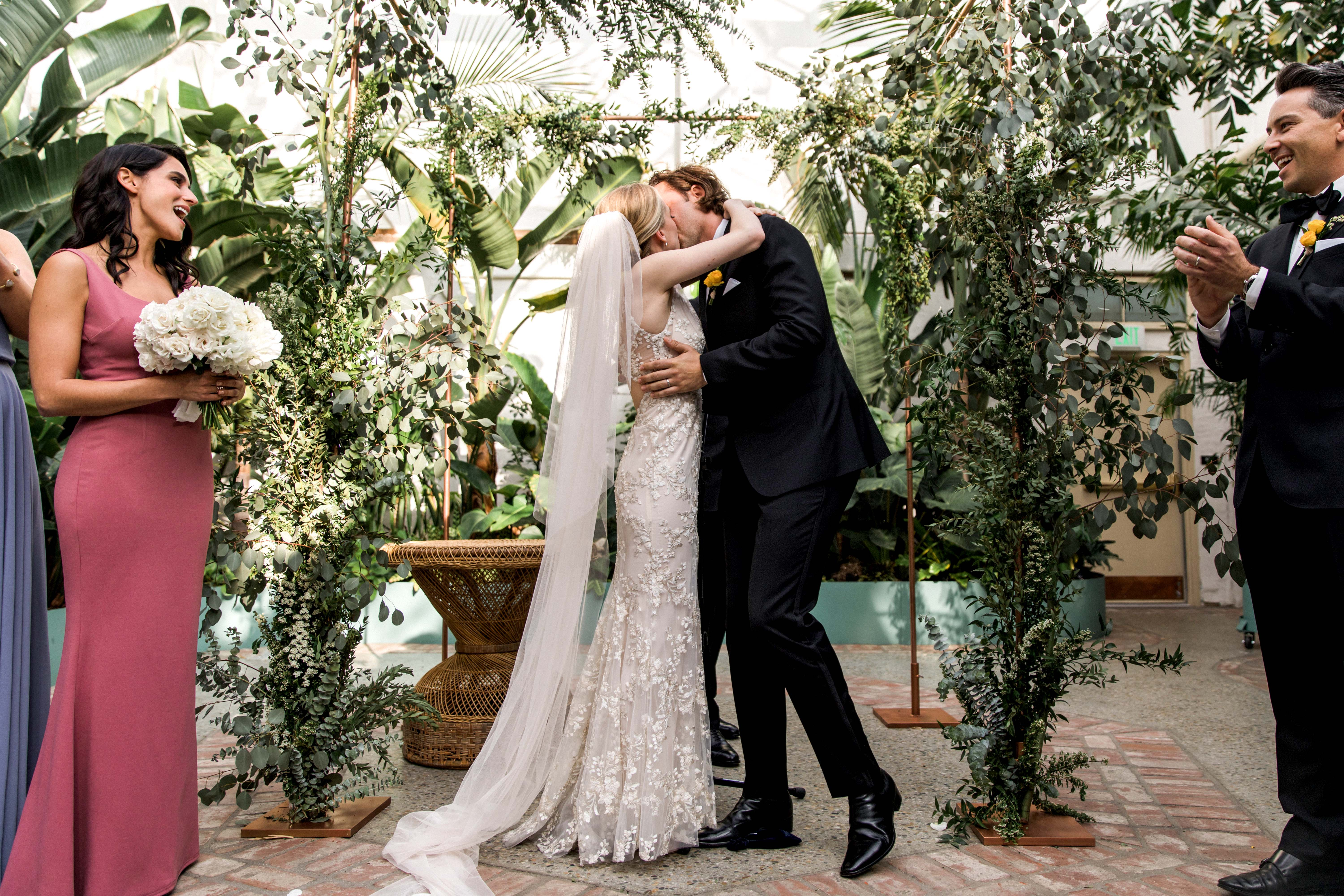 bride and groom kiss ceremony plants backdrop