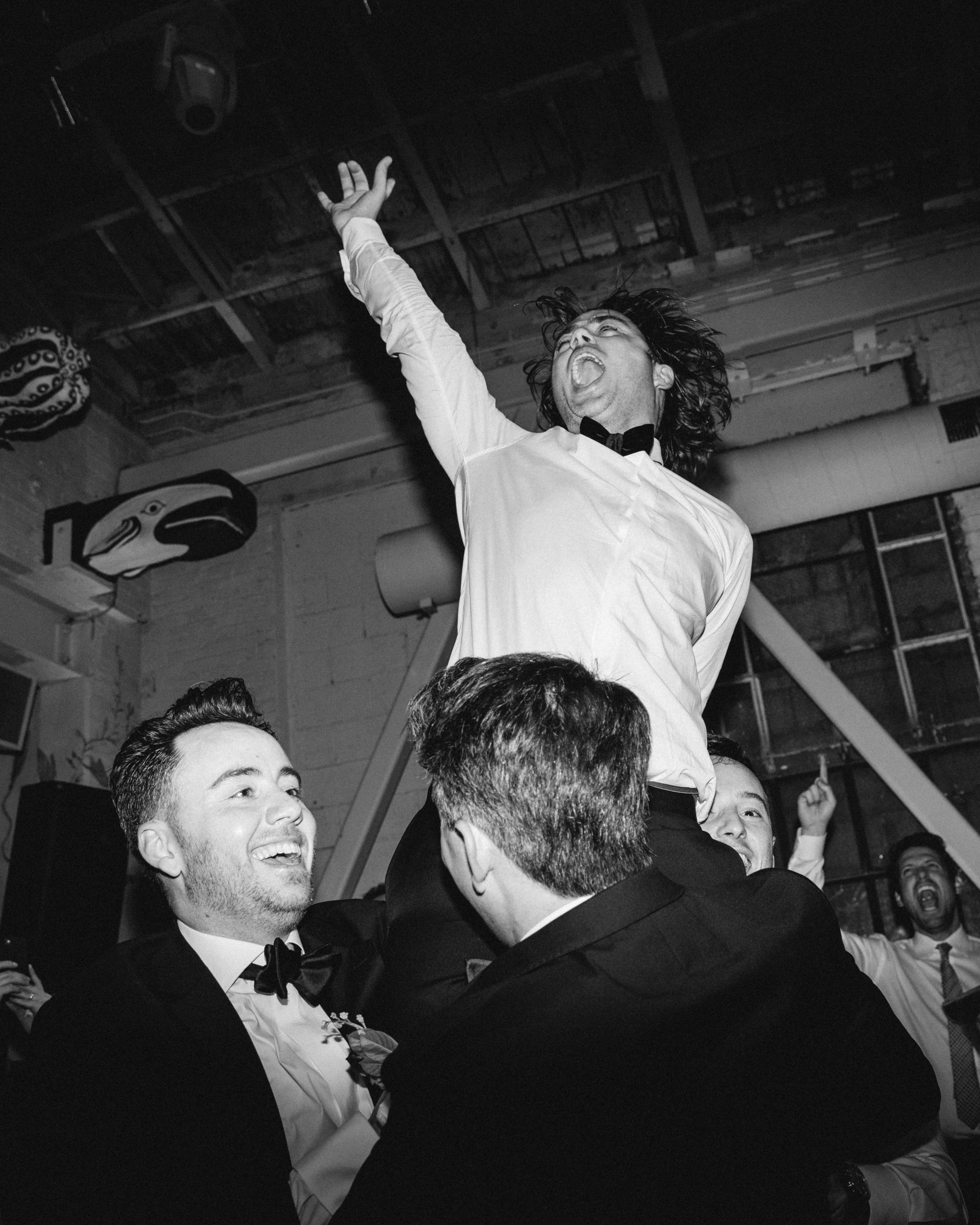 groom and groomsman dancing wedding reception