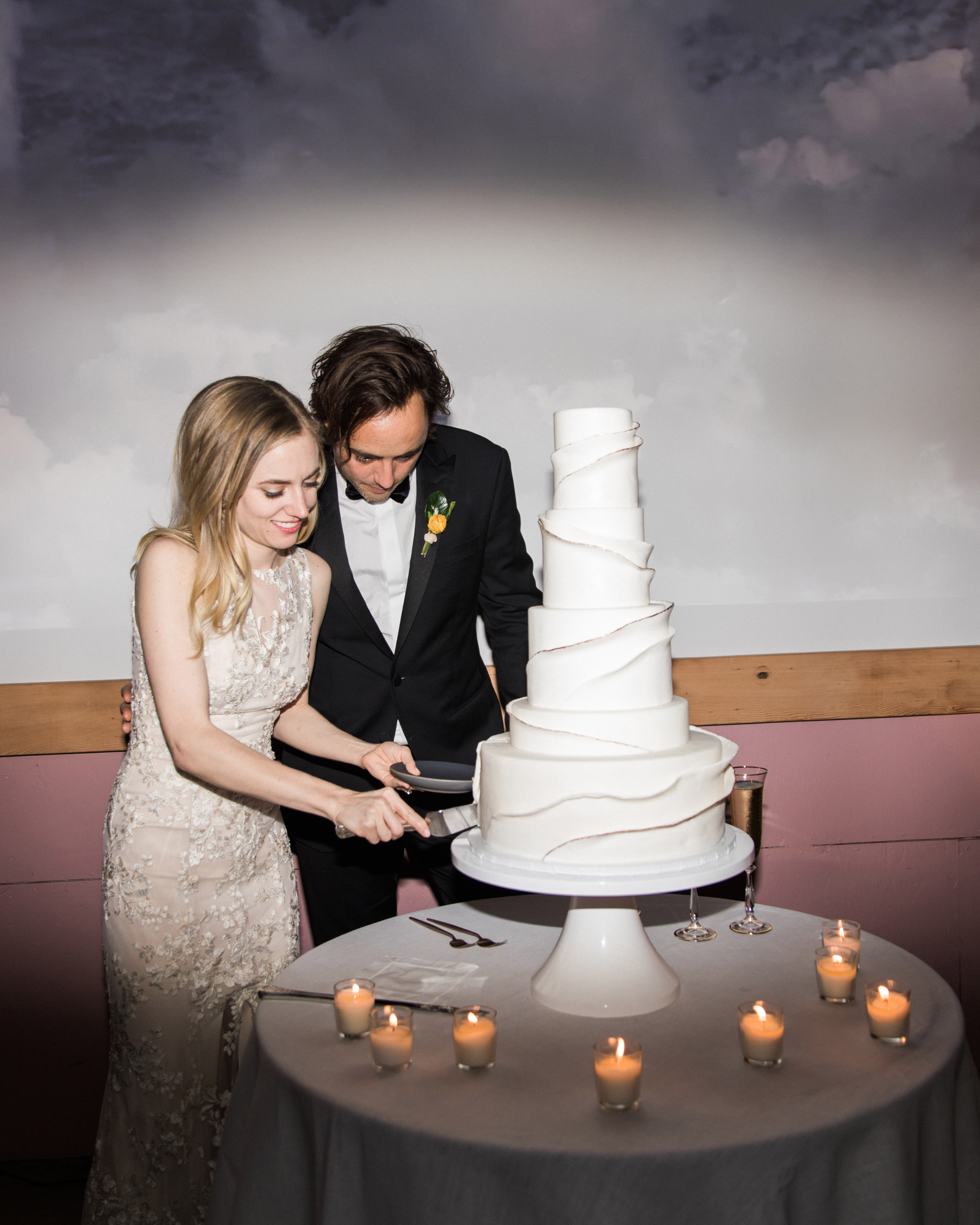 bride groom slicing tiered wedding cake surrounded by small candles