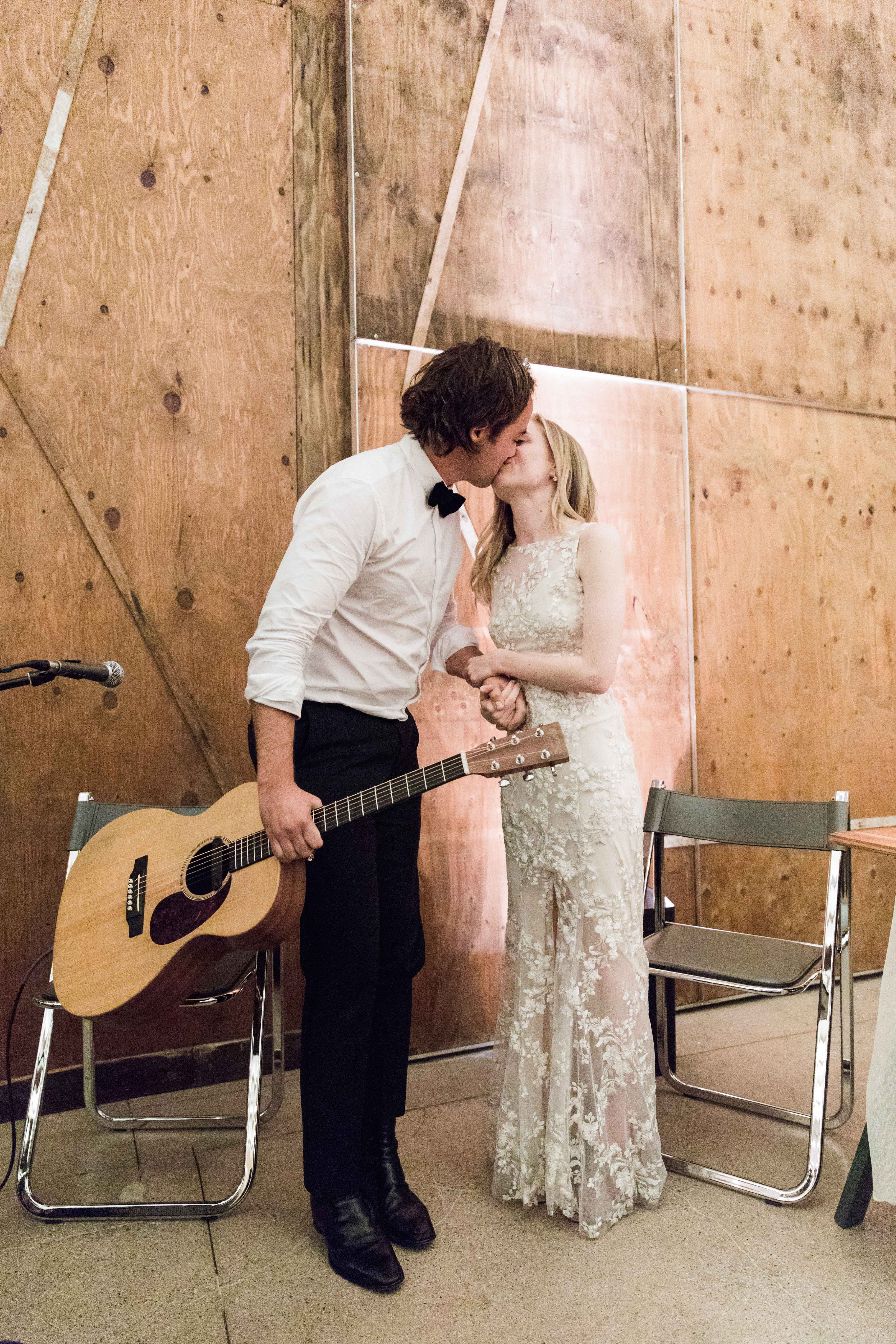 wedding couple kissing groom holding guitar
