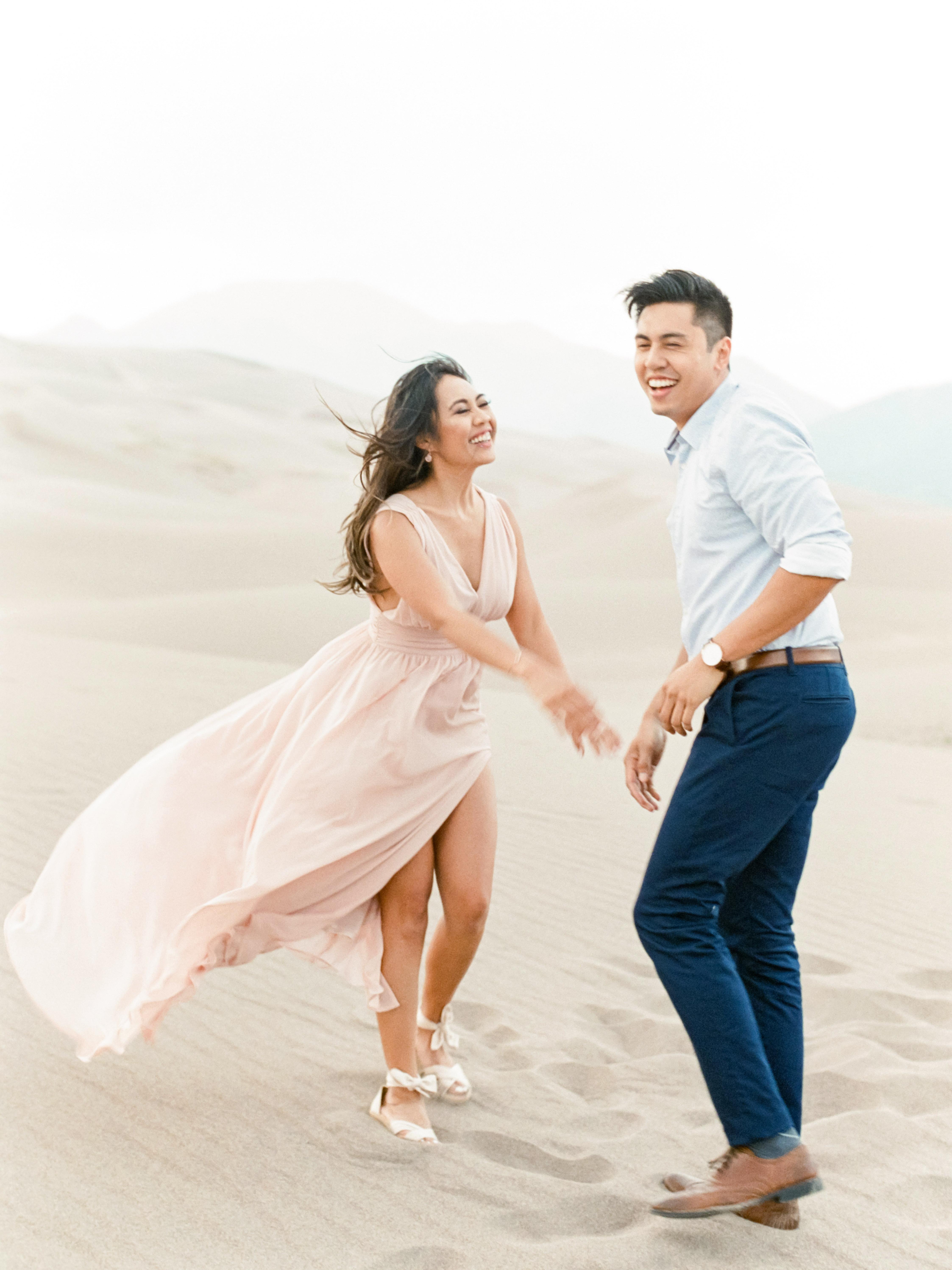 destination engagement couple walking sand dunes colorado